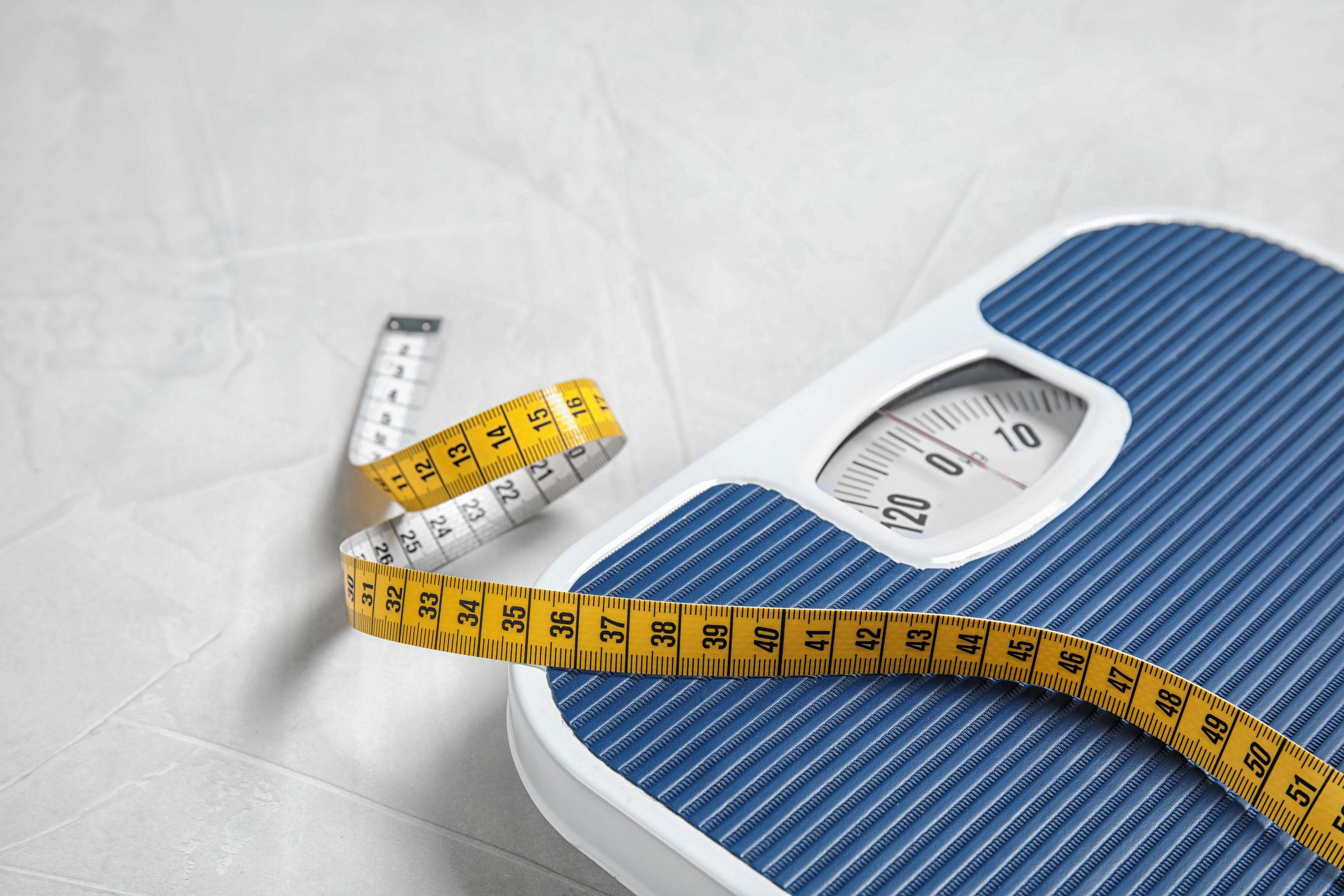 Imagem de uma balança com uma fita métrica em cima