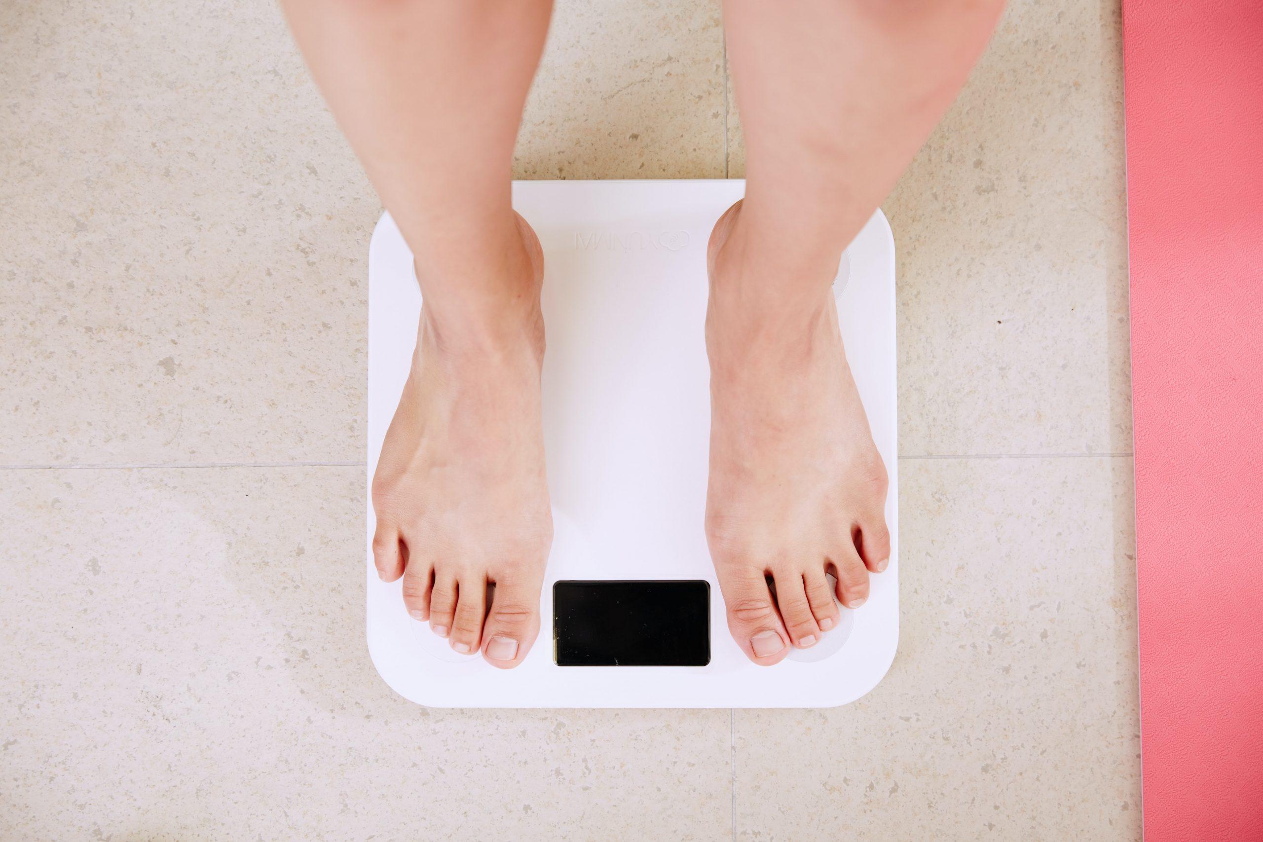 Imagem mostra pés femininos sobre uma balança.