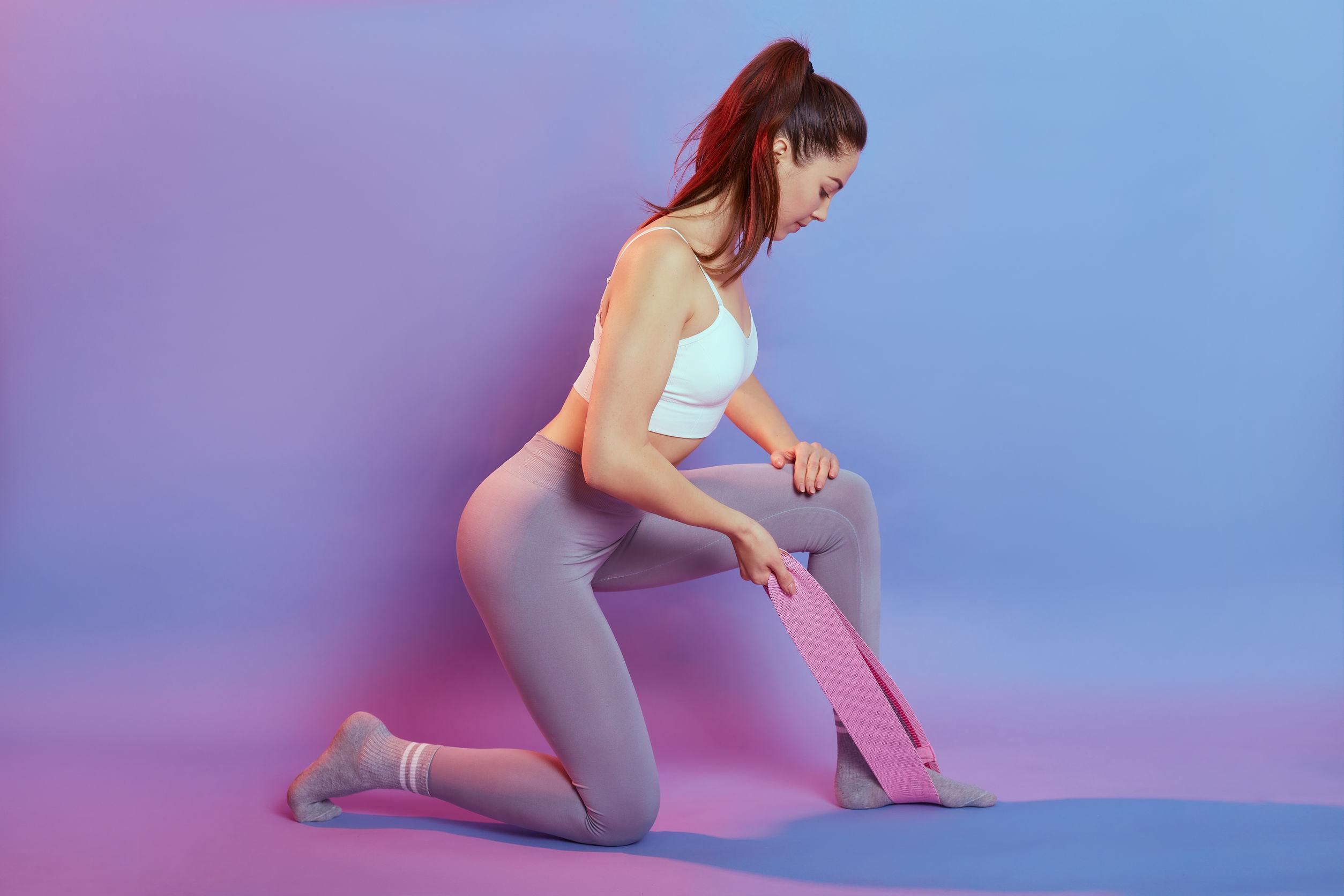 Mulher com roupa fitness realizando exercício com mini band