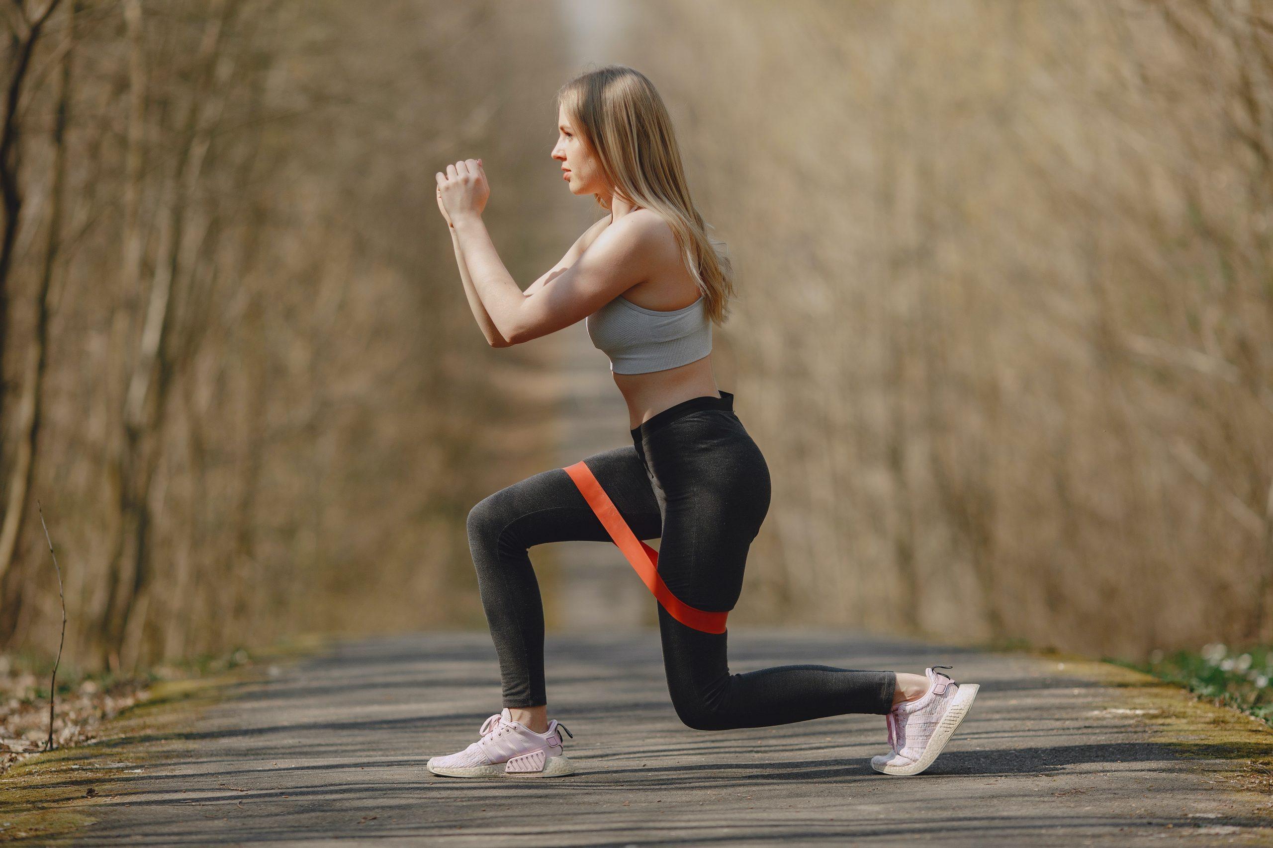 Jovem loira praticando exercício com Mini Band ao ar livre