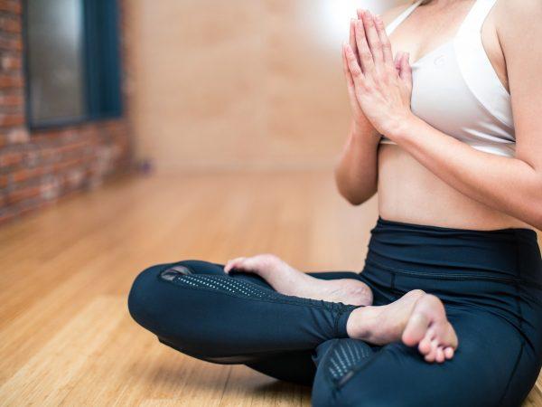 Imagem mostra uma mulher praticando ioga em casa.