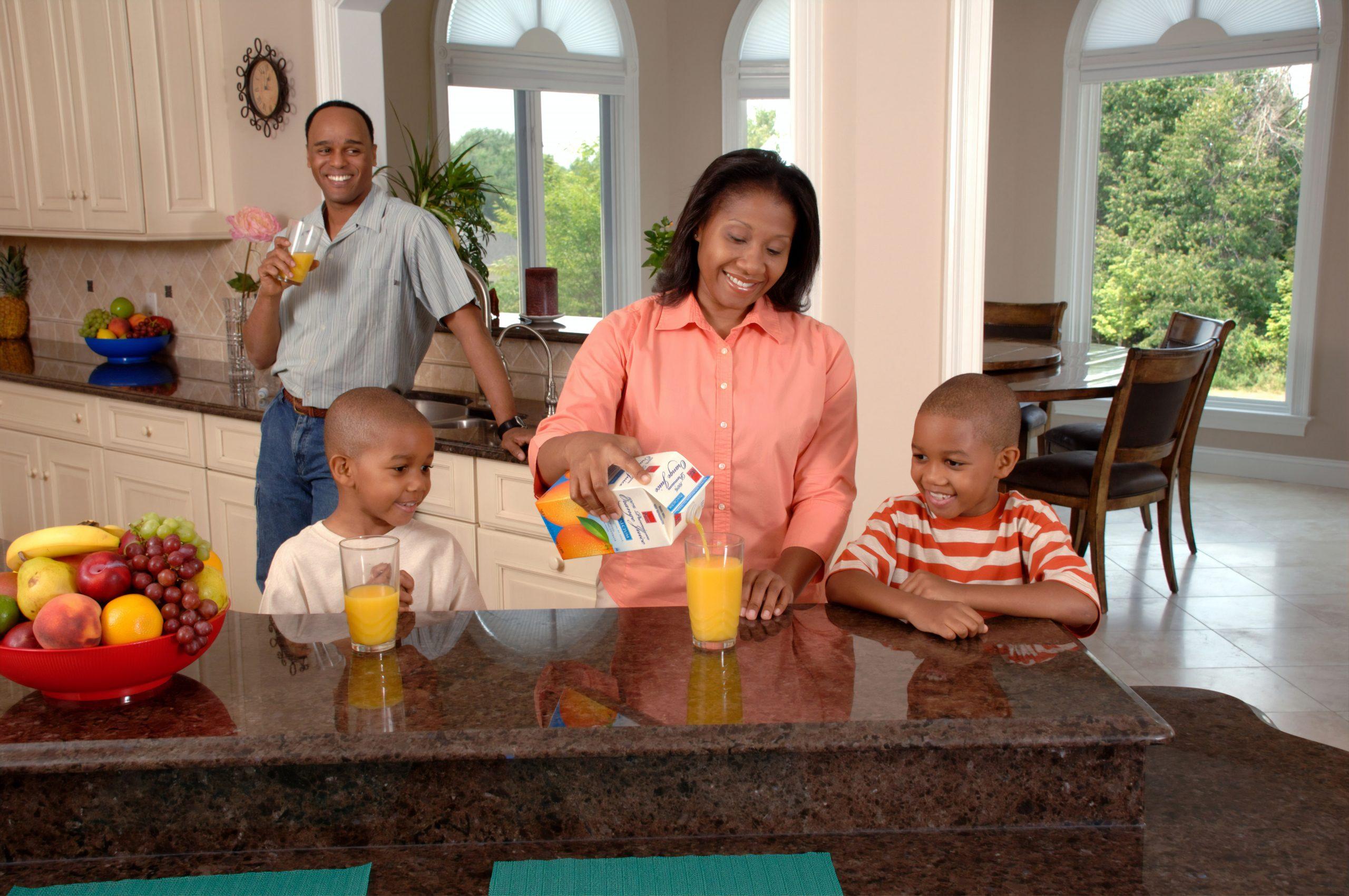 Imagem mostra mãe servindo suco de laranja para os filhos na cozinha