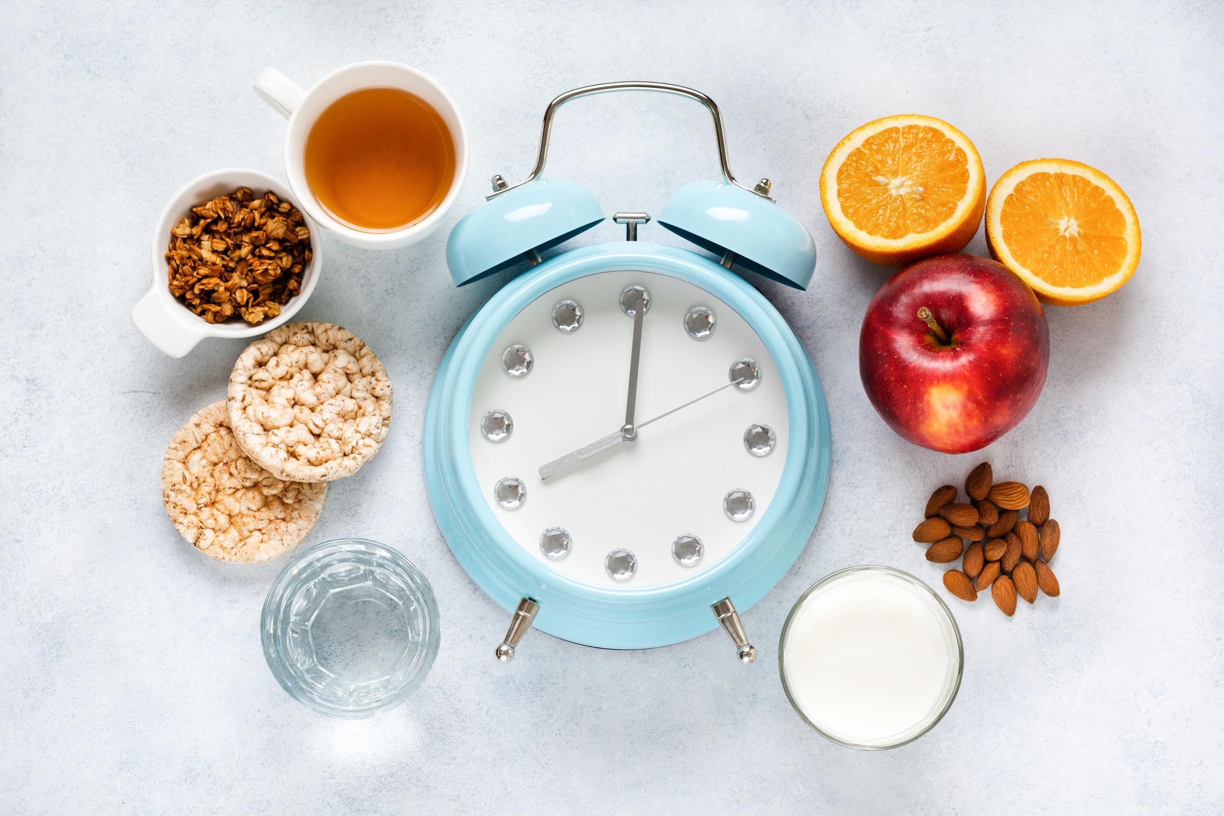 alimentos e relógio na bancada para controlar o jejum intermitente