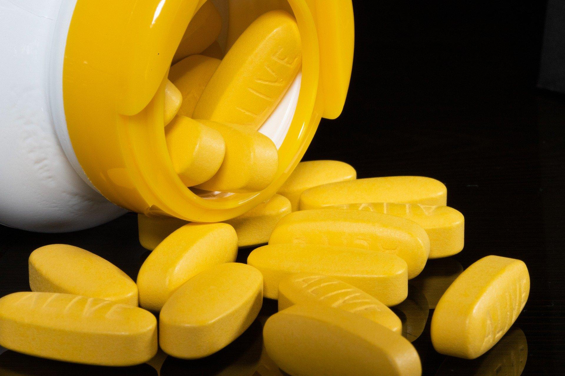 Imagem mostra várias cápsulas amarelas saindo de um frasco.