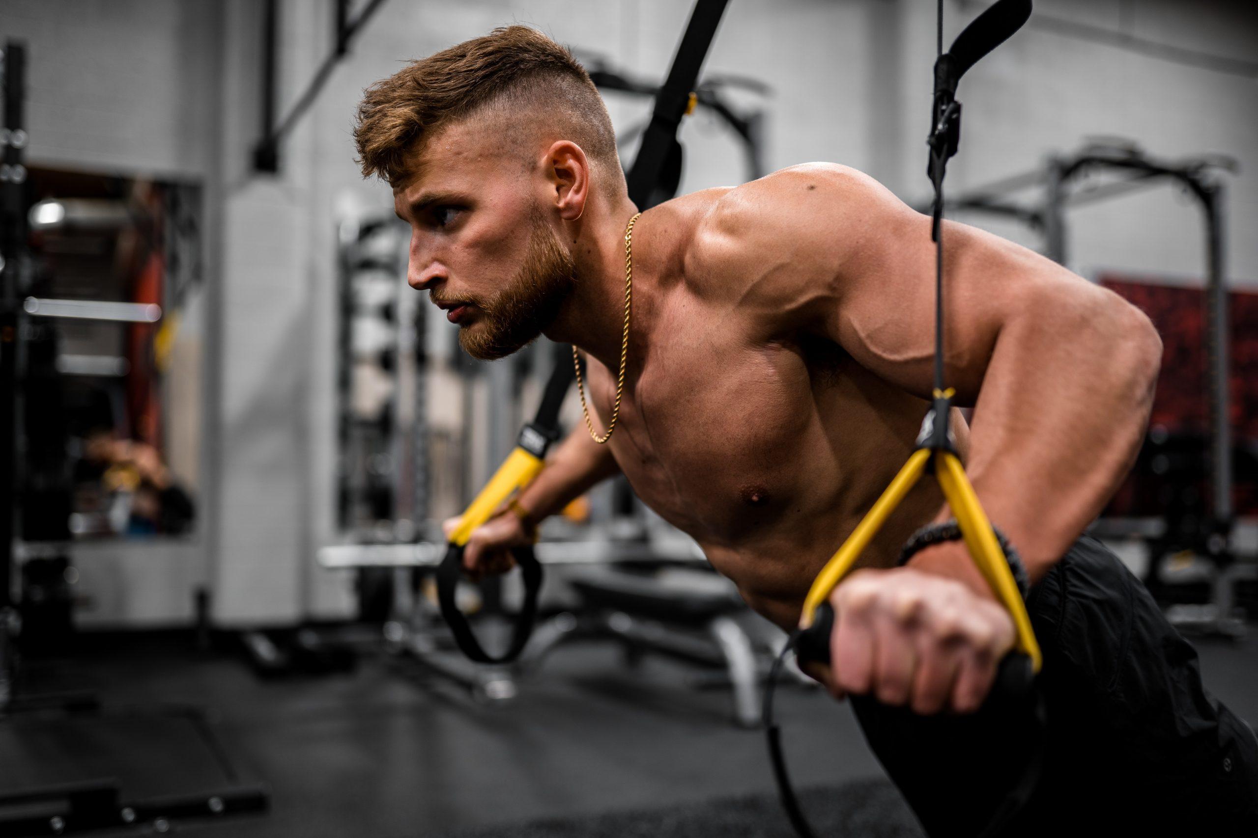 Homem sem camisa pratica exercício no TRX