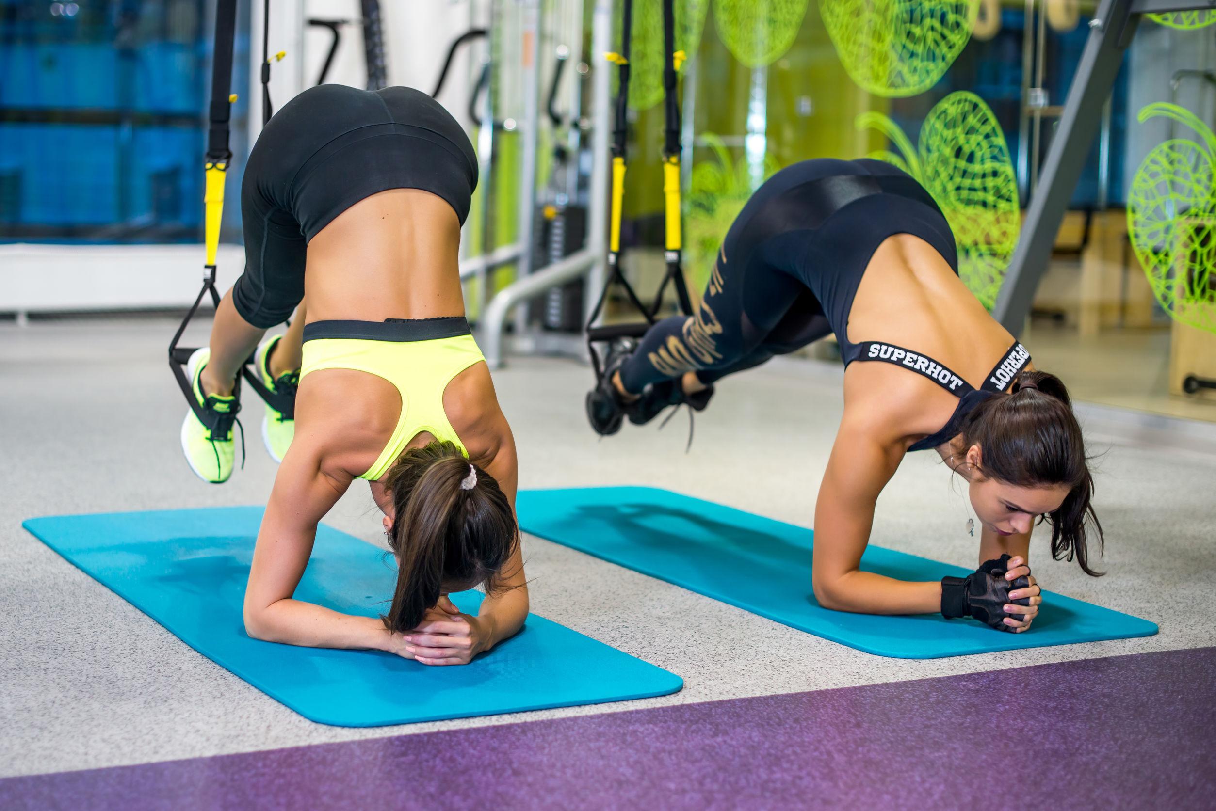 Duas mulheres realizando exercício com um TRX em uma academia