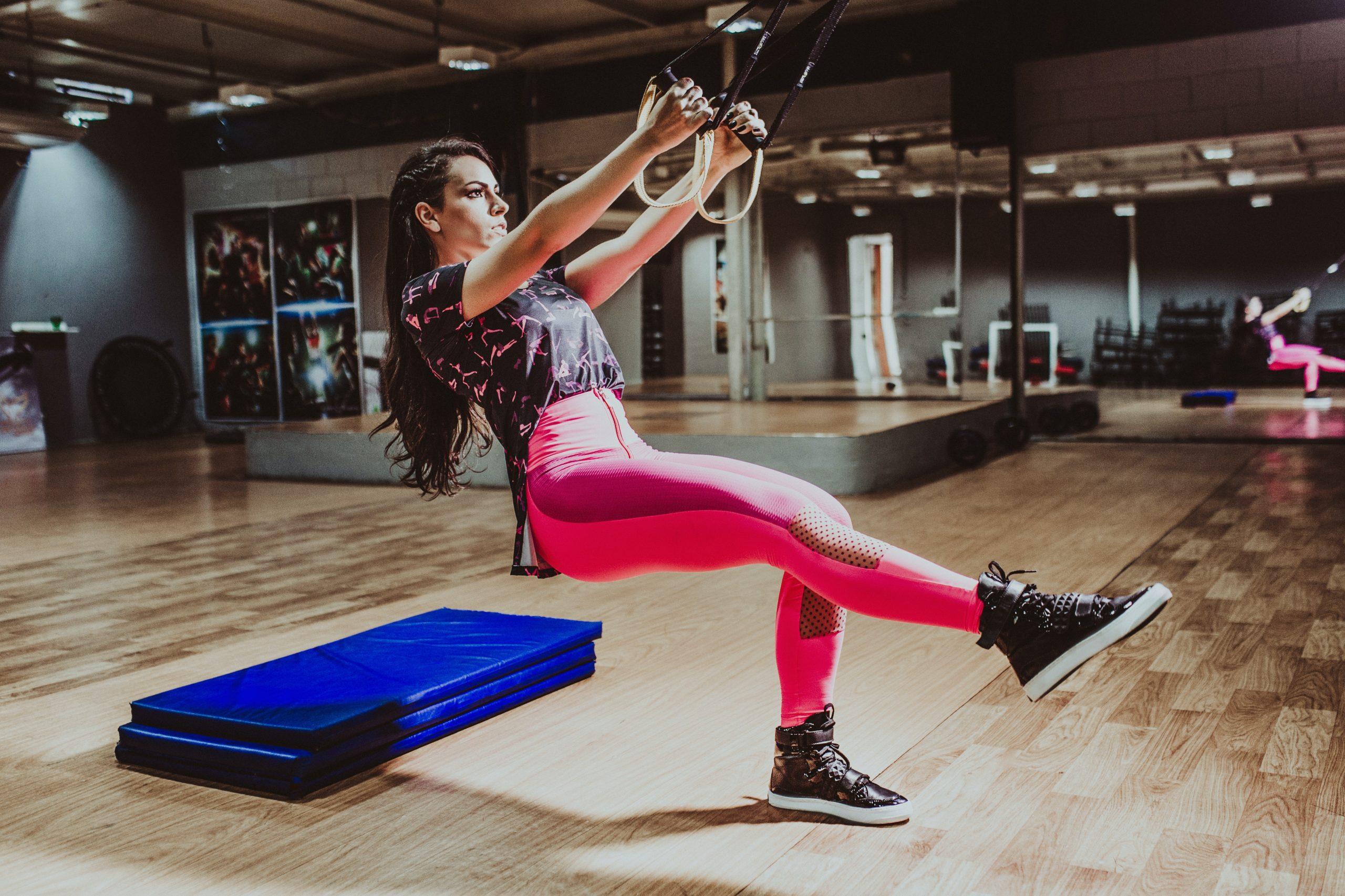 mulher com roupa de ginástica realizando exercício no TRX em uma sala de academia.