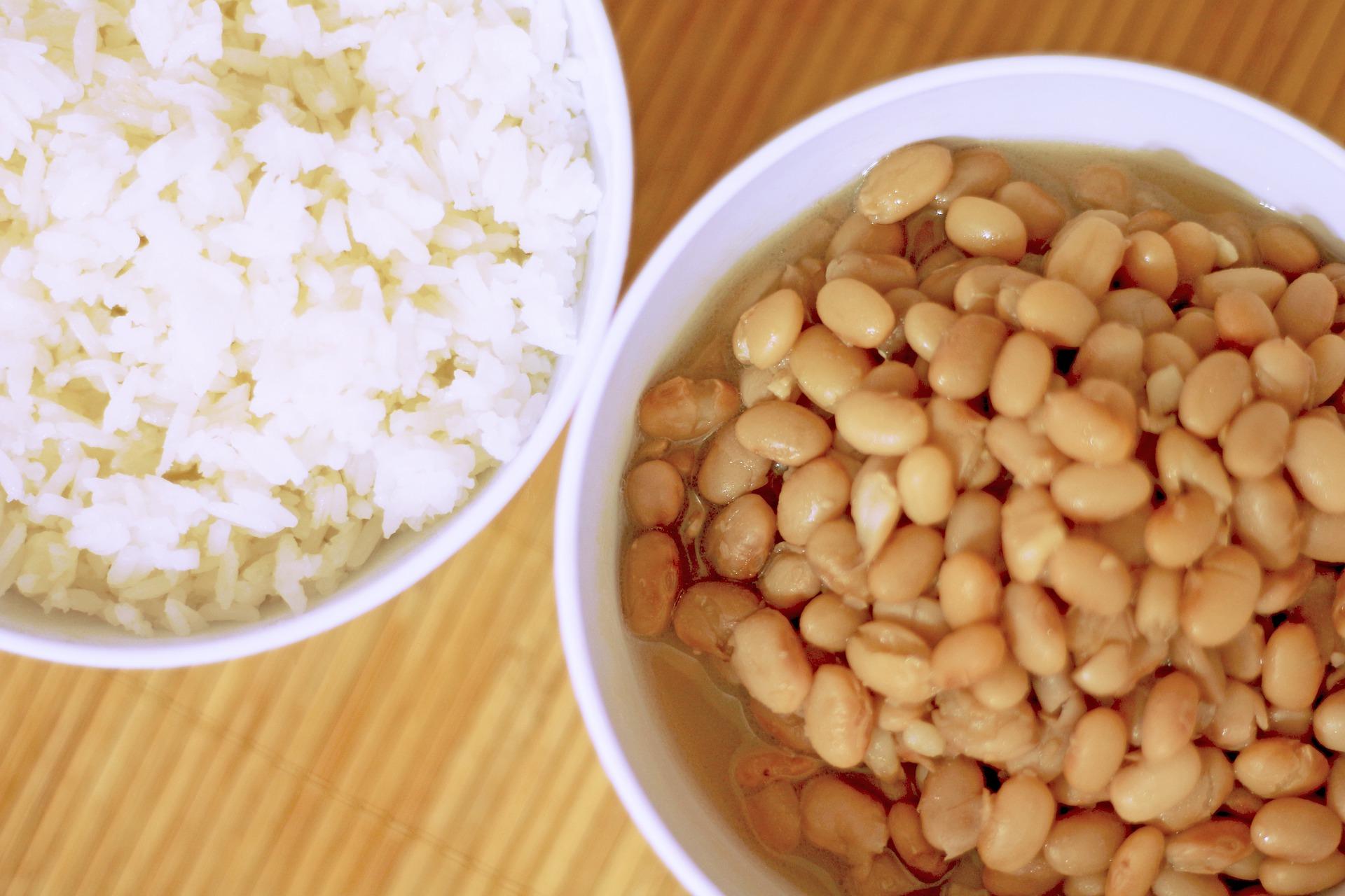 Imagem mostra uma cumbuca com arroz e uma com feijão lado a lado.