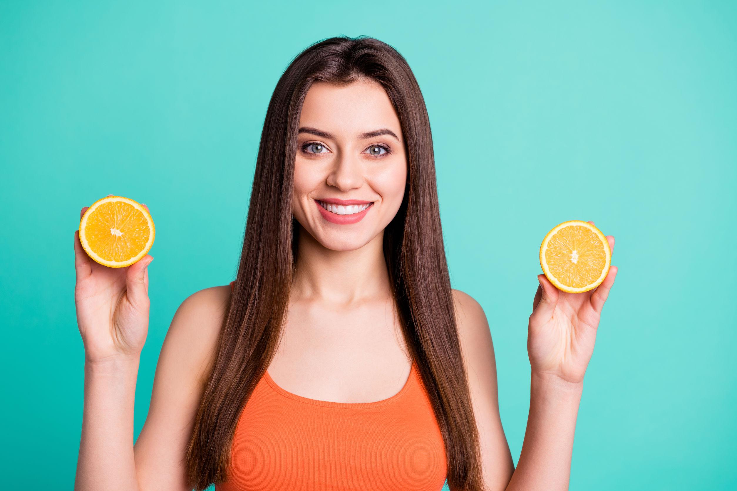 Imagem de uma mulher segurando duas metades de uma laranja.