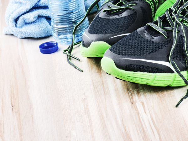 Pair of sport shoes and water bottle. After workout setting