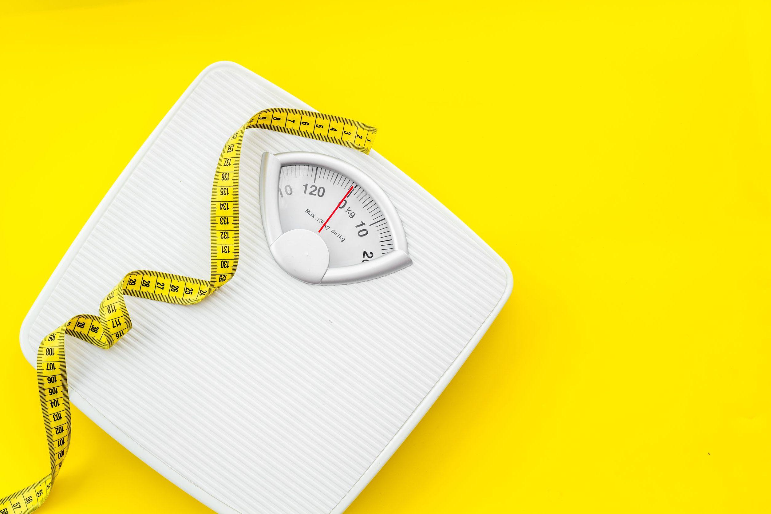 Imagem de uma balança com uma fita métrica.