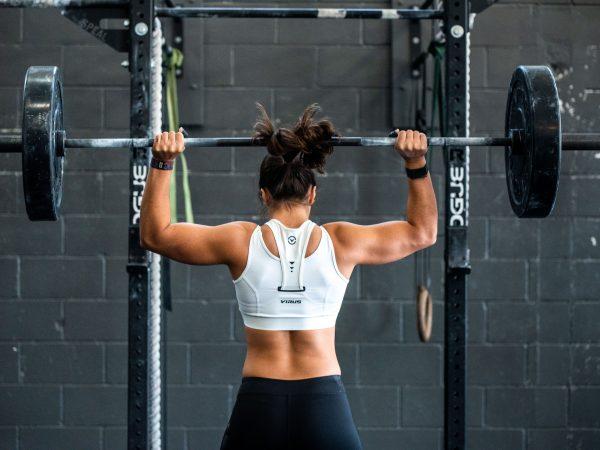 Imagem de uma mulher de costas treinando com levantamento de peso.