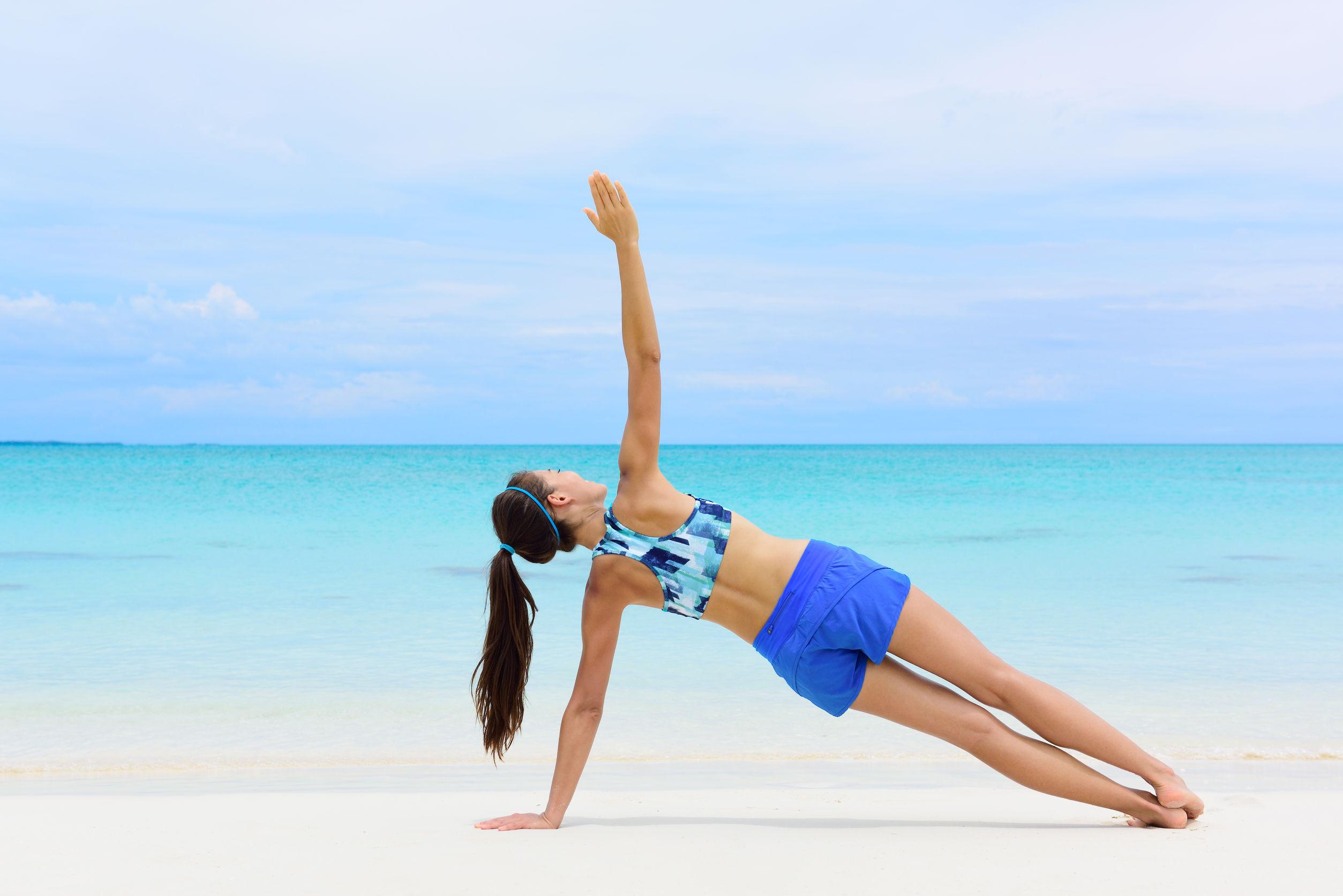 mulher na beira da praia praticando exercícios para o quadril