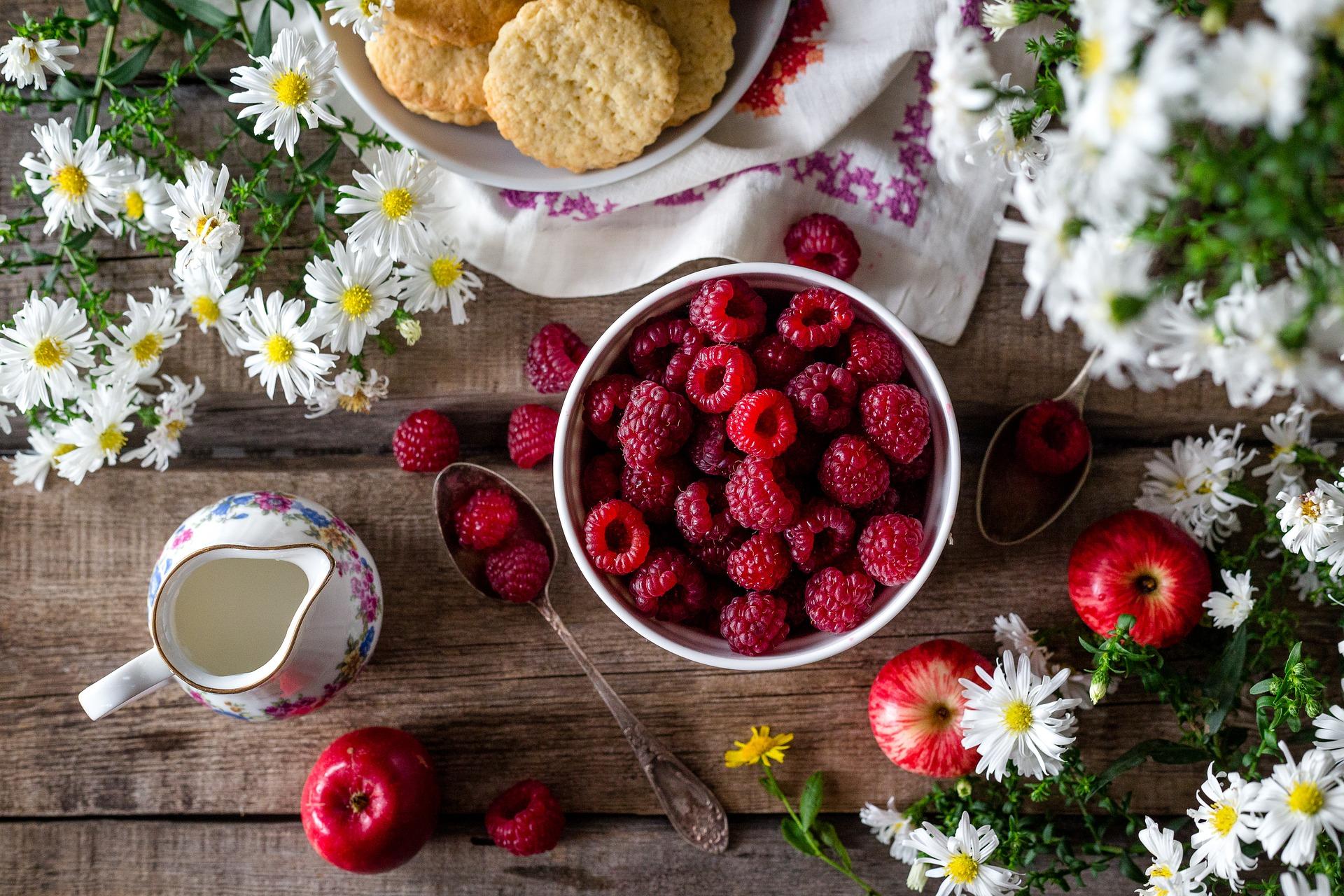 Tigela com framboesas e maçãs, biscoitos, leiteira e flores.