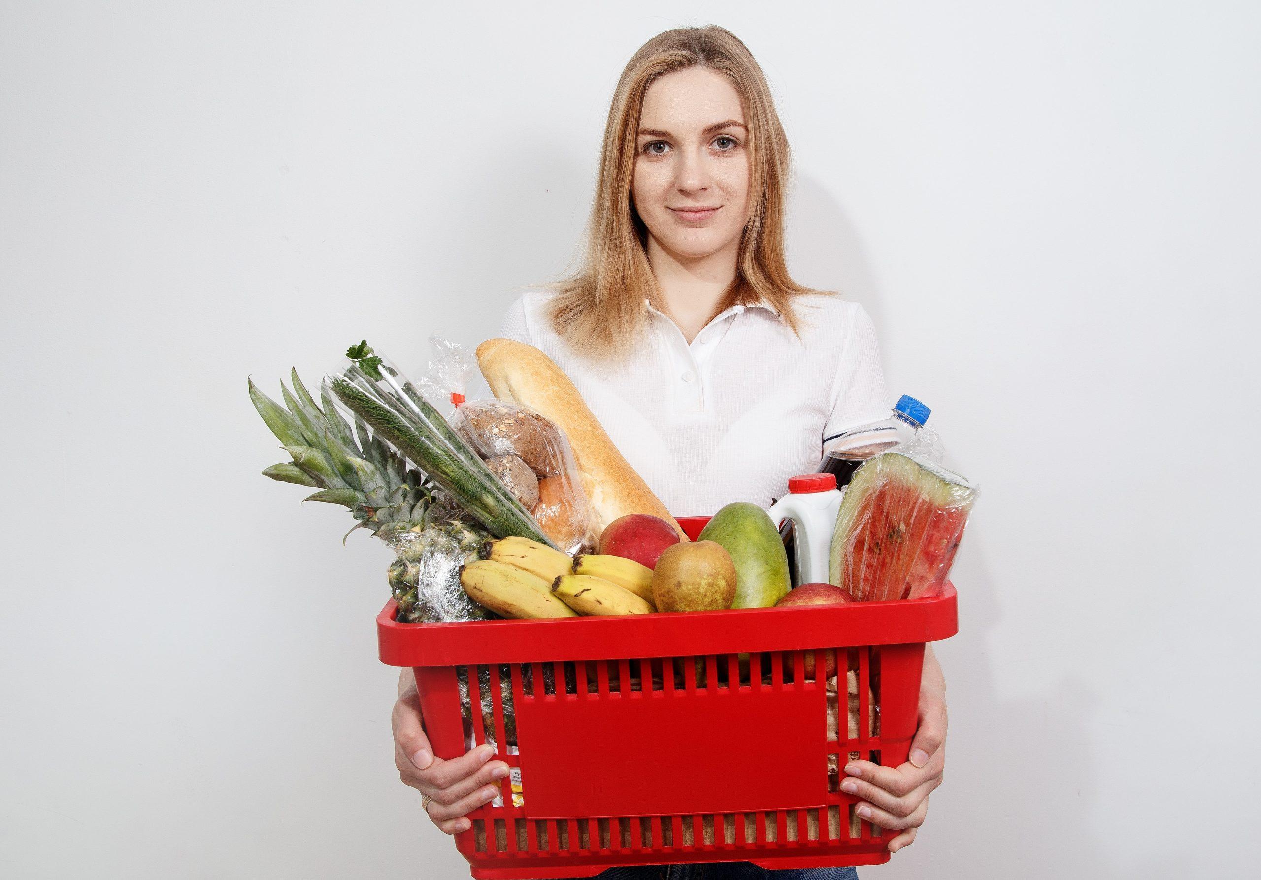 Mulher segurando cesta com frutas e outros alimentos.