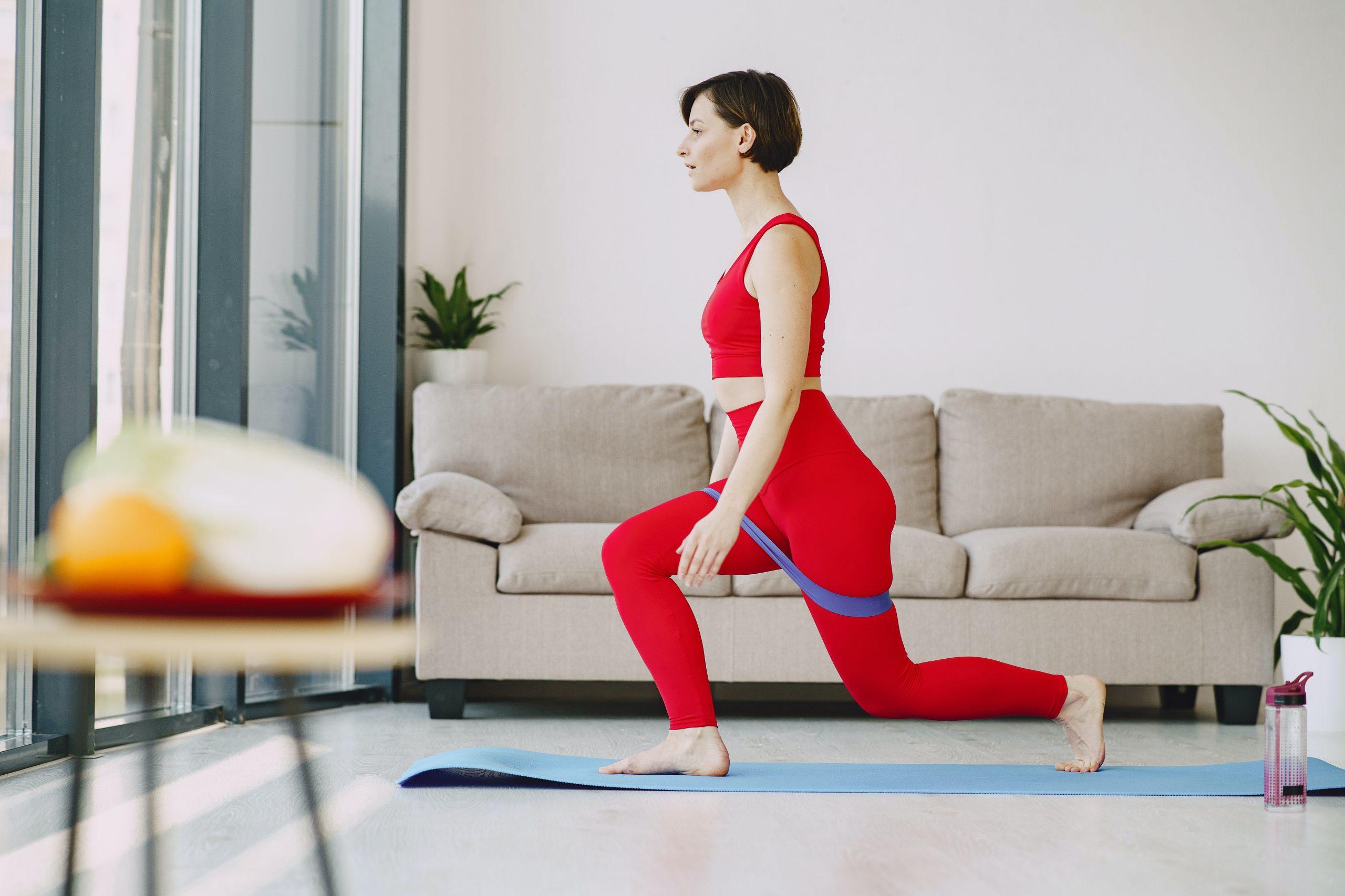 Imagem de uma mulher se exercitando com uma faixa elástica.