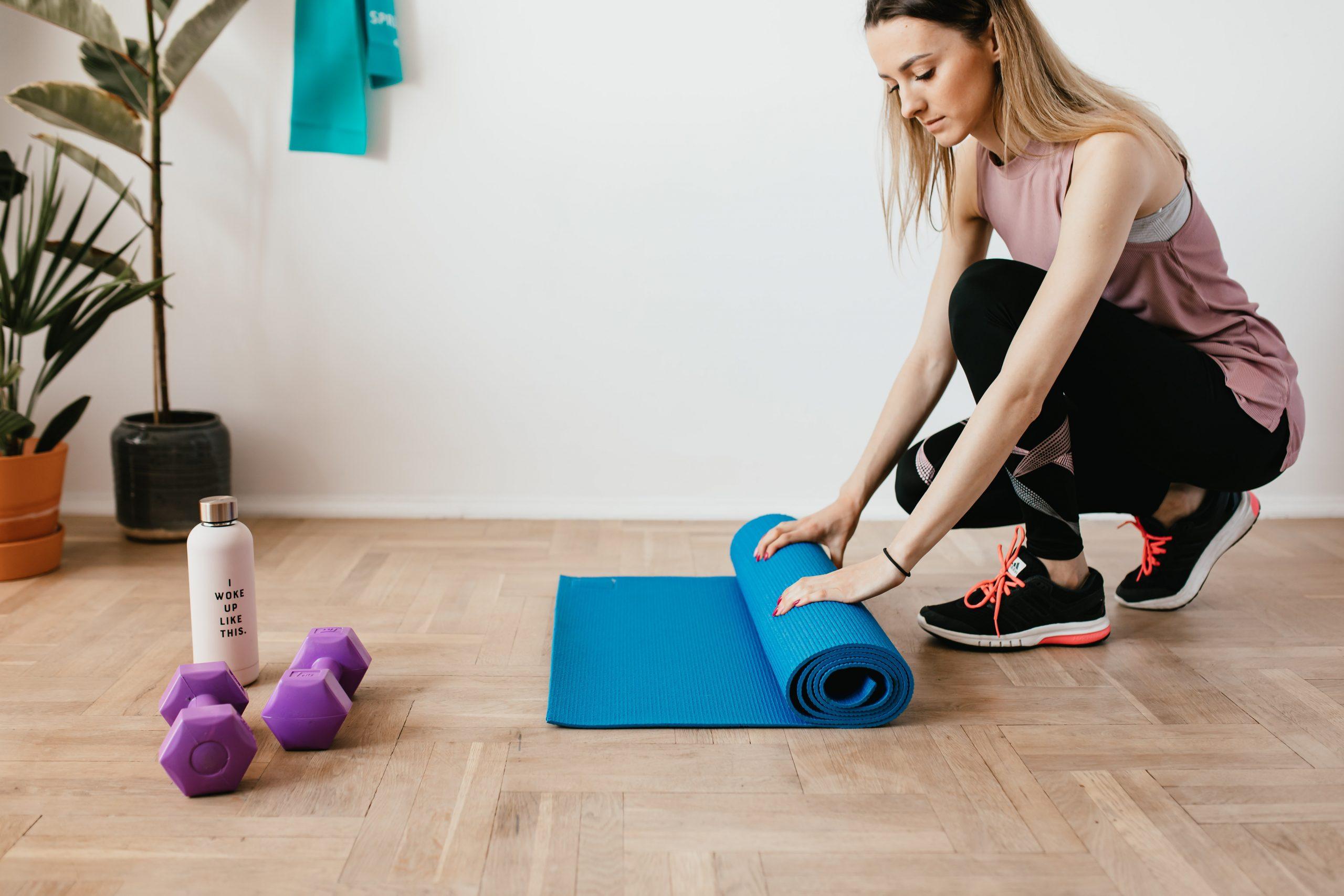 Imagem de uma mulher enrolando um tapete de exercício.