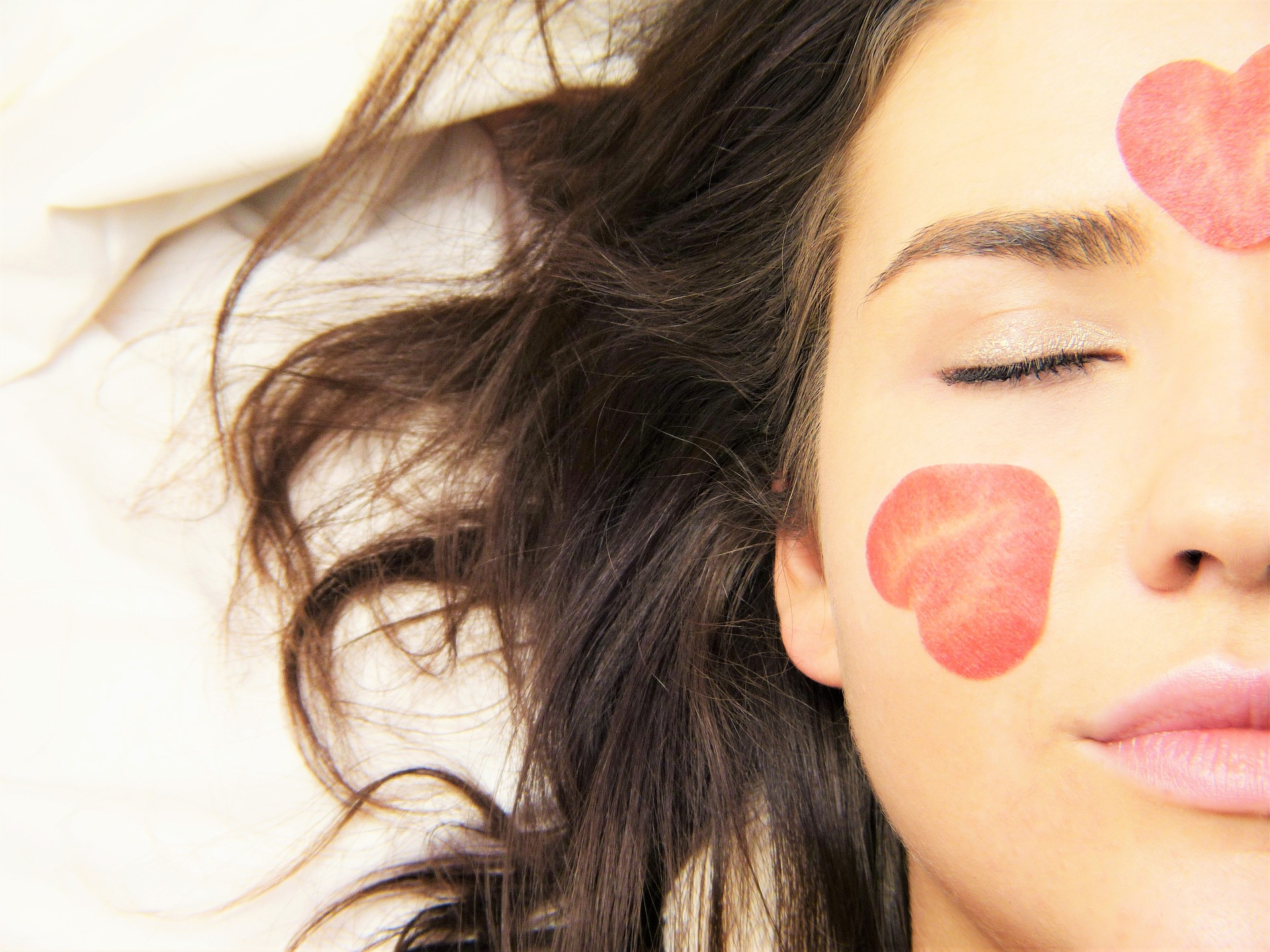 Mulher com pétalas de flor no rosto.