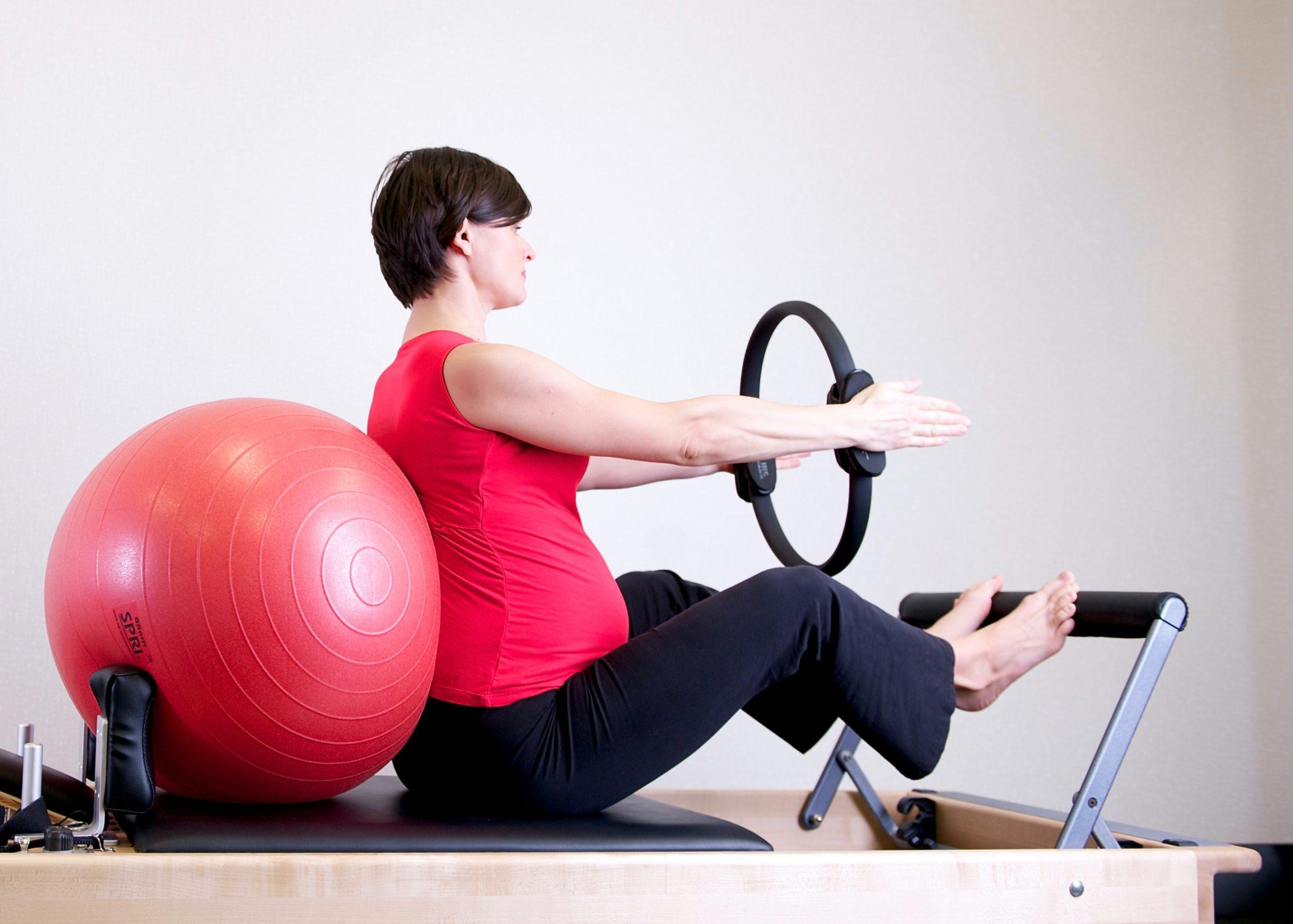 Imagem de uma mulher grávida fazendo pilates.