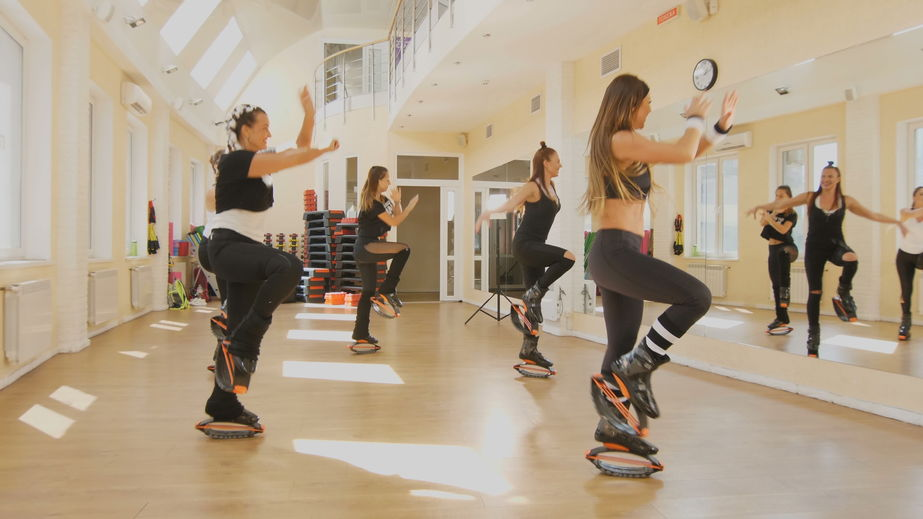 Mulheres fazendo aula na acadmeia de ginástica com kangoo jump.
