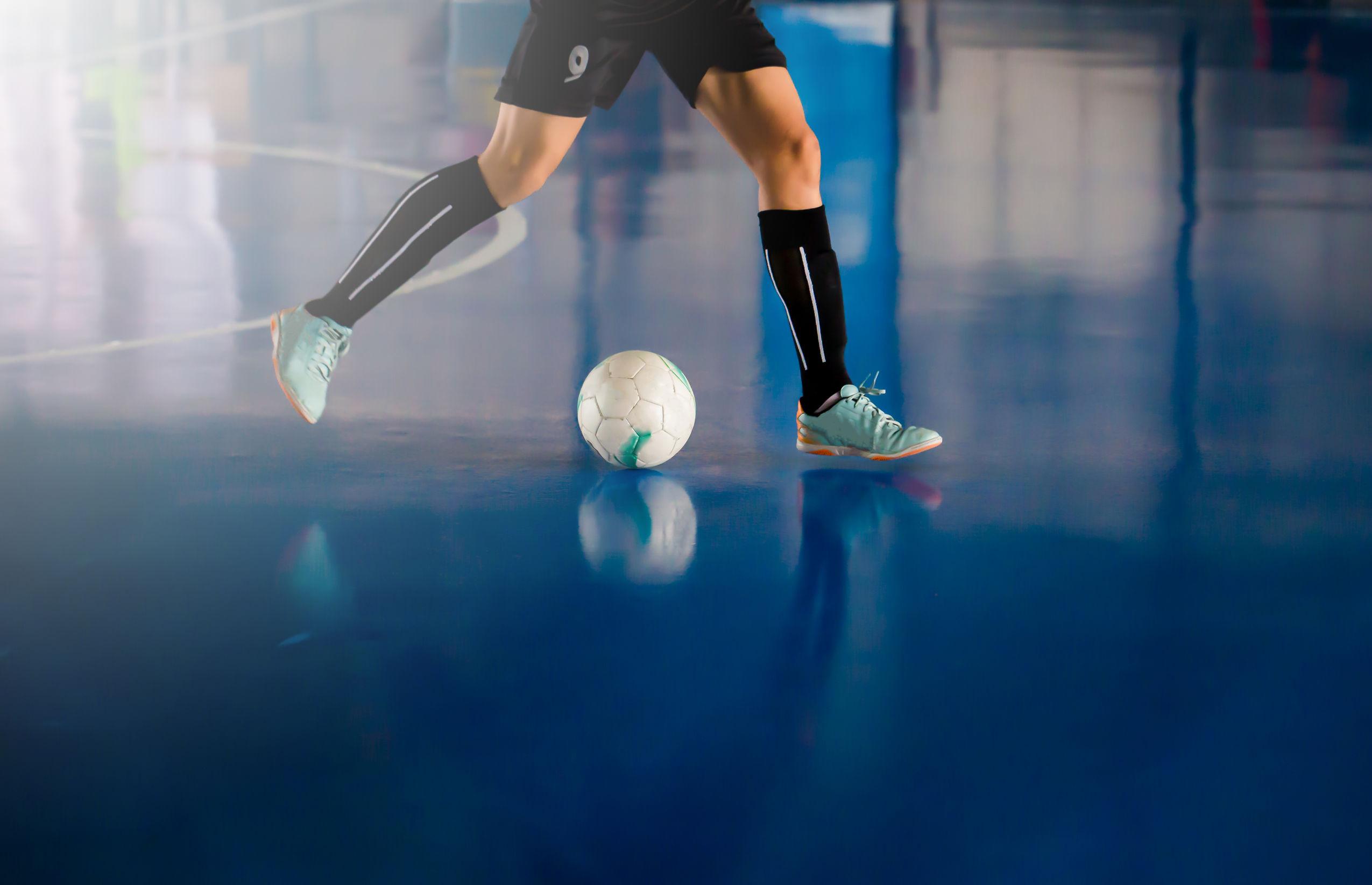 Jogador em uma quadra de futsal com o domínio da bola