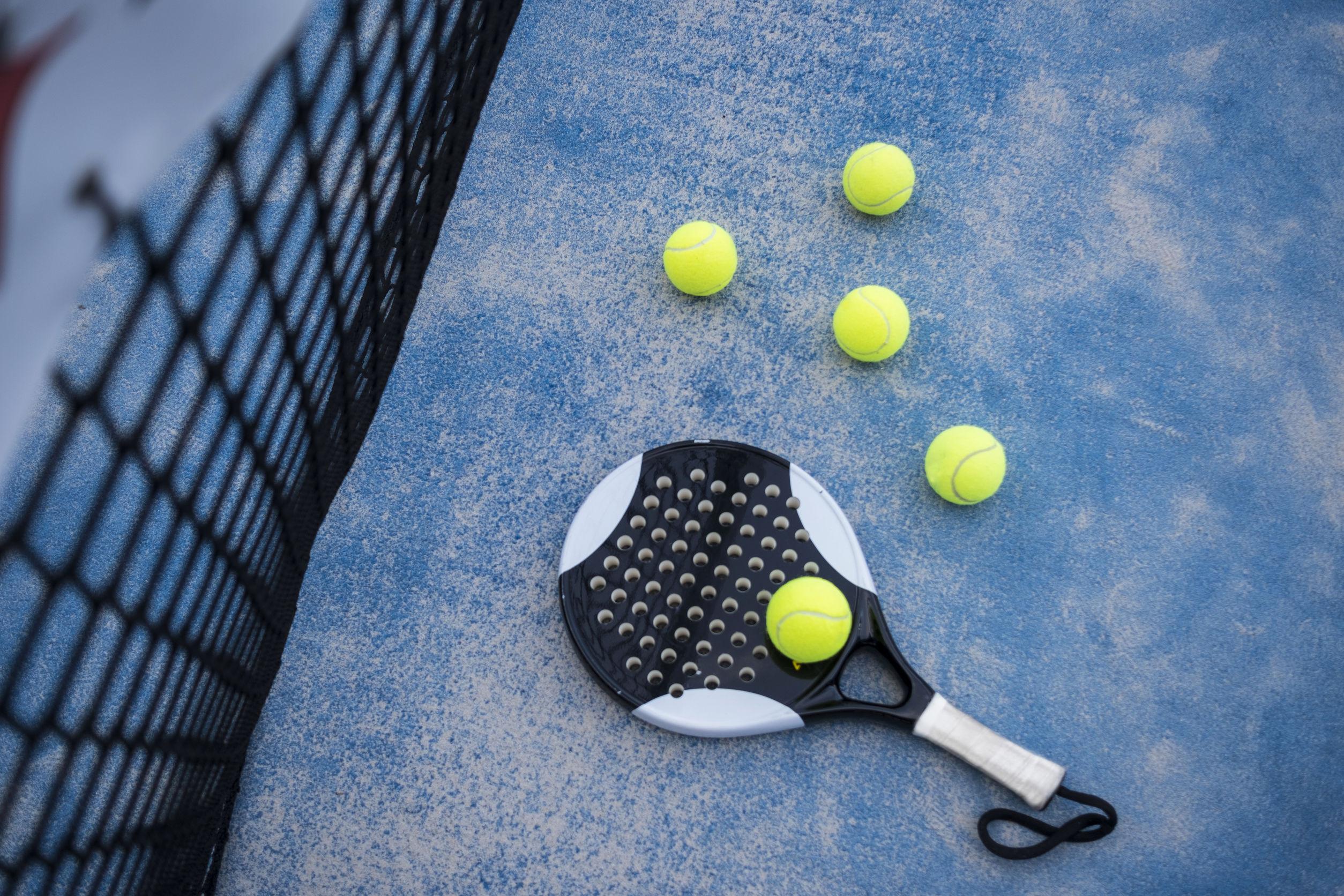 Raquete de padel e três bolas de tênis em cima de um chão azul e de uma rede de jogo