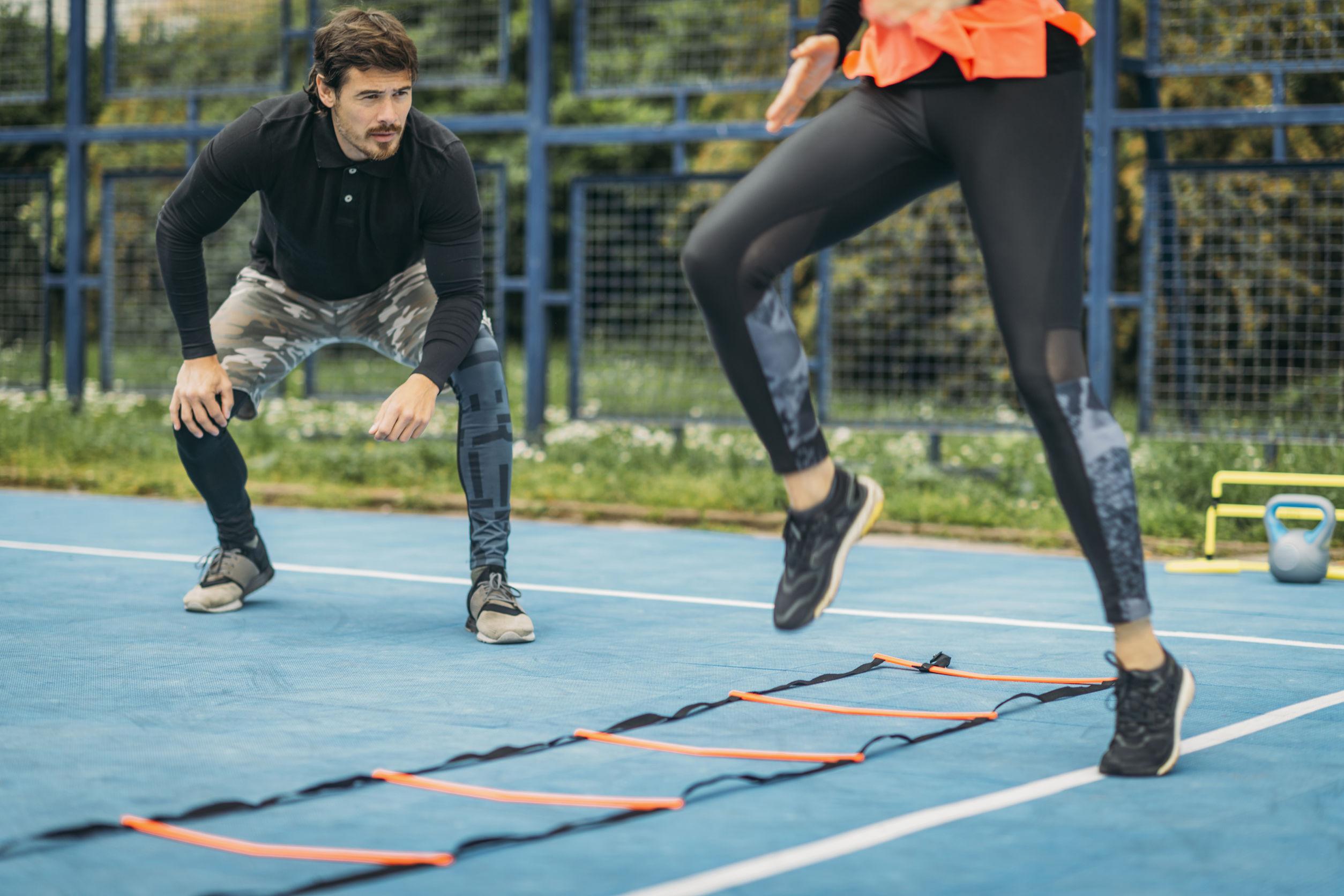 Imagem de uma mulher treinando em uma escada de agilidade com o auxílio de um treinador.