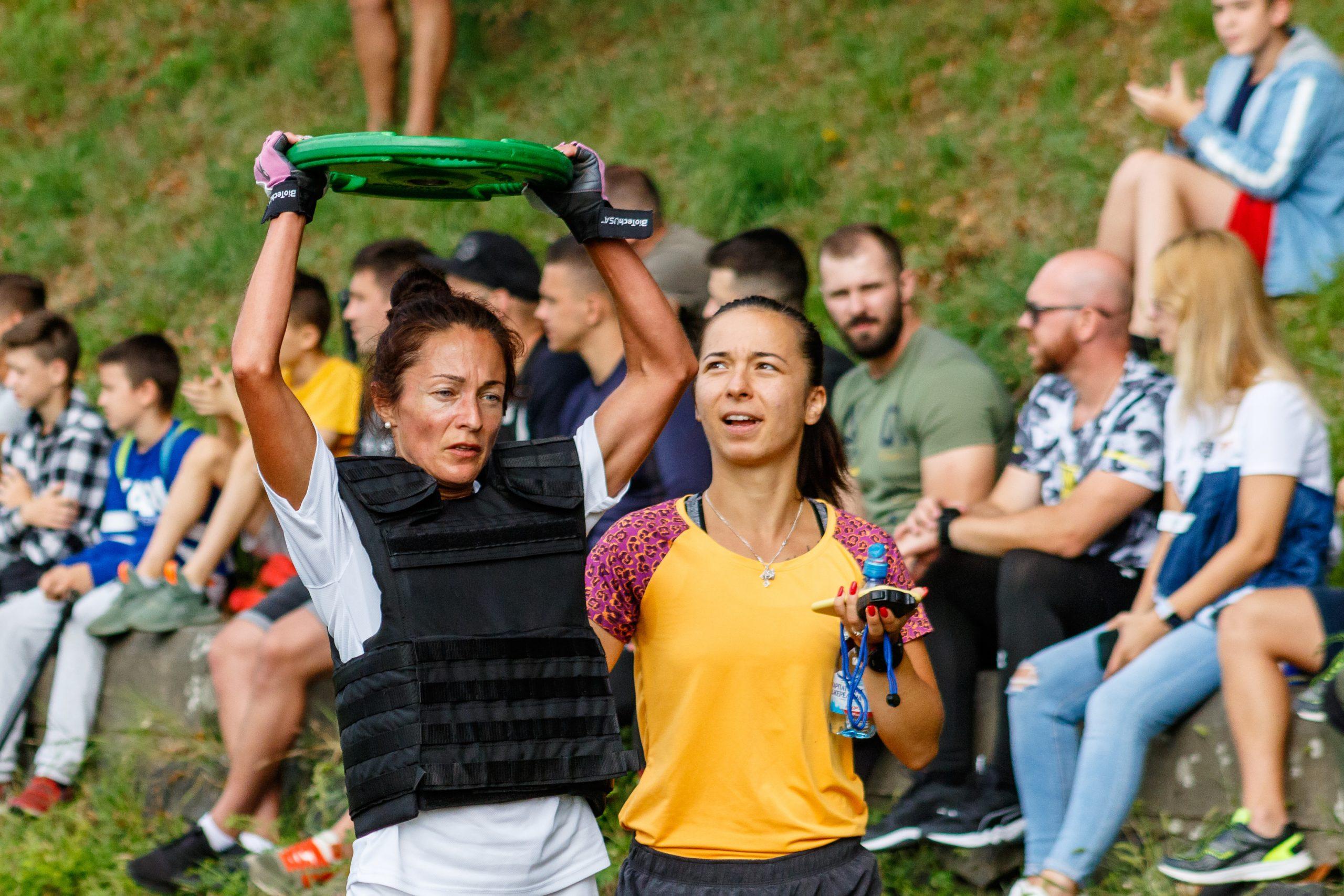 Mulher usando colete de peso participando de prova de crossfit.