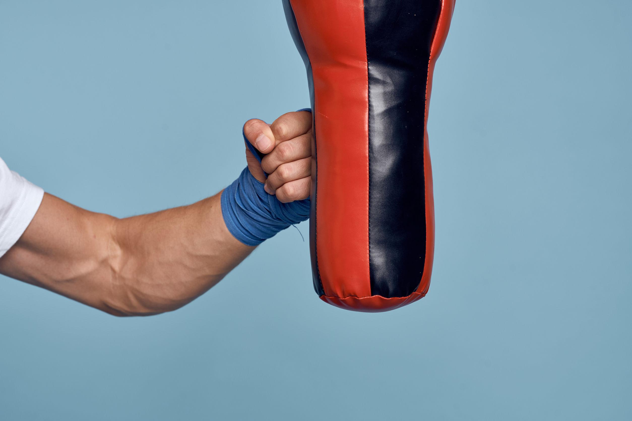 Homem com luvas de academia dando um soco no punching ball