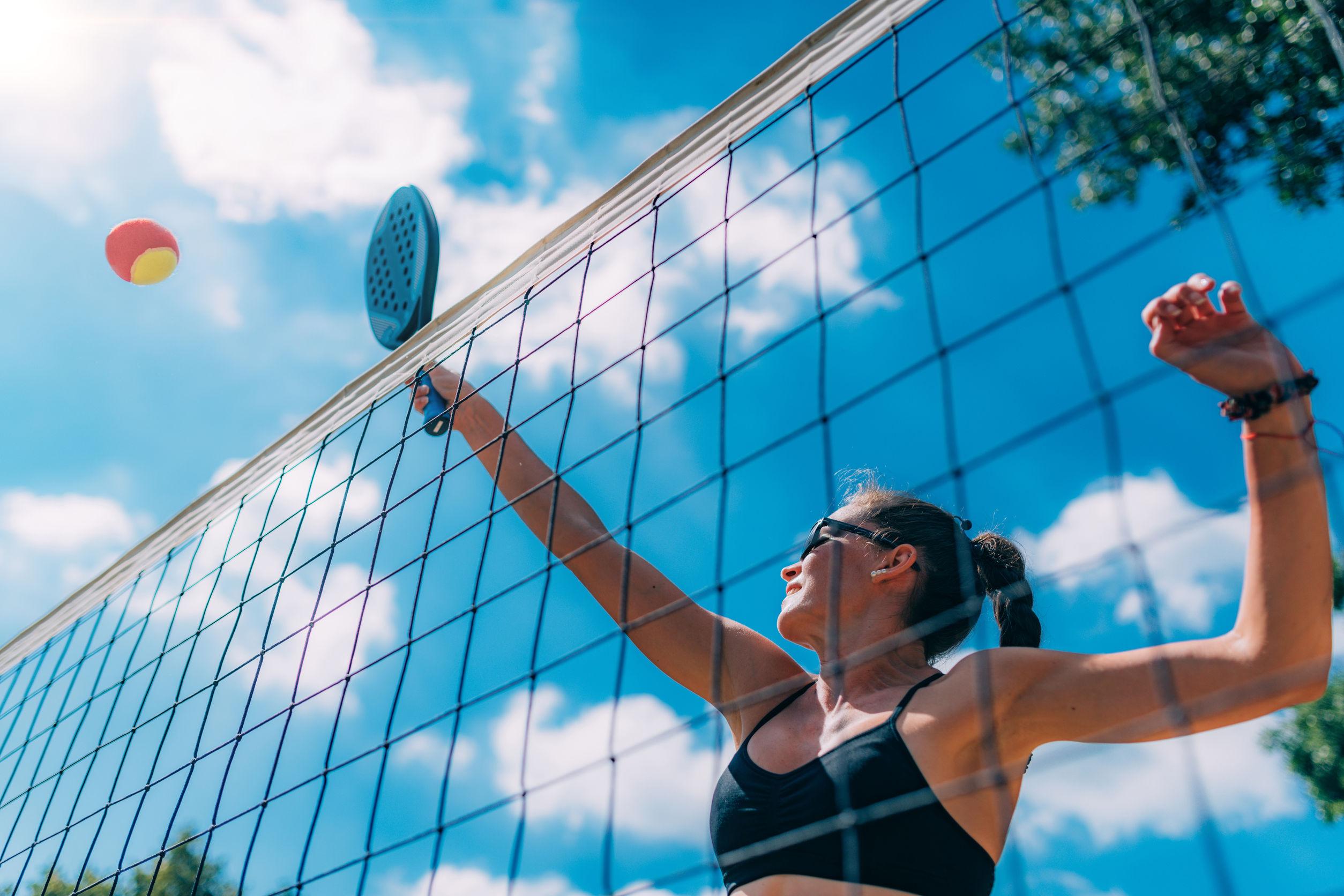 Imagem de uma mulher jogando tênis de praia.