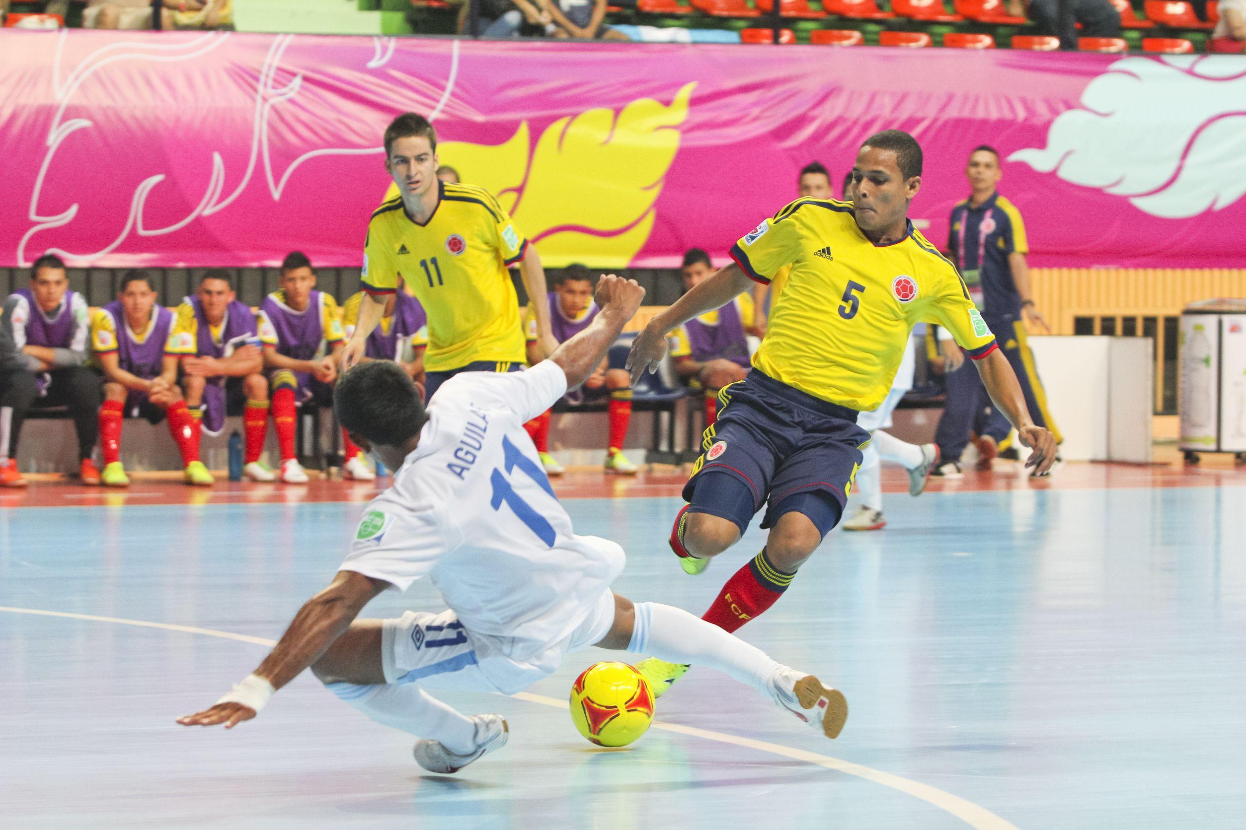 Foto do mundial de Futsal FIFA em 2012. Jogo entre Guatemala e Colômbia. Jogadores estão disputando a bola.