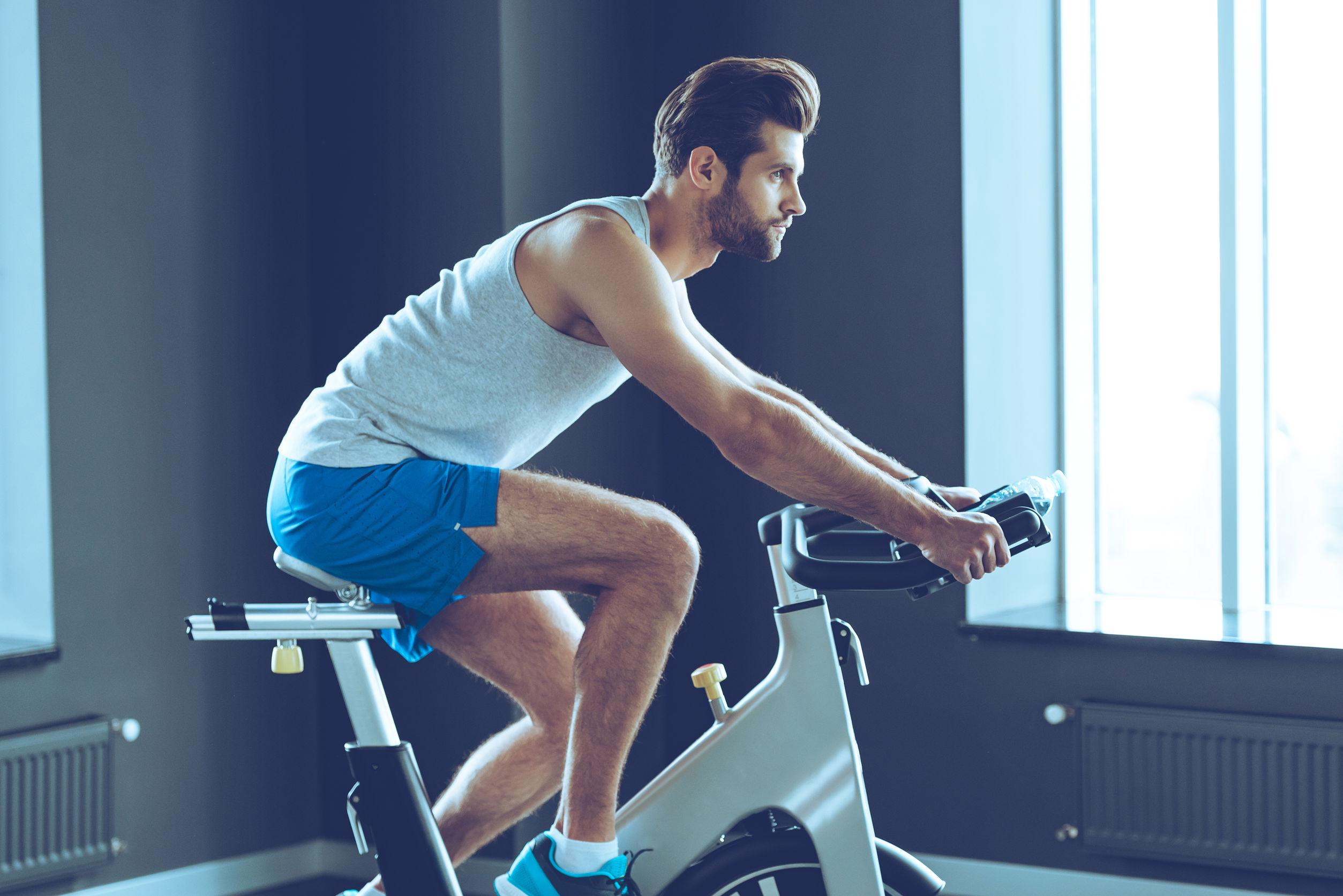Homem sem blusa em uma academia fazendo exercício na bicicleta