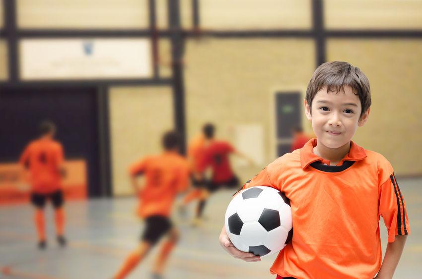 Foto de um menino olhando para a Câmera e segurando uma bola de Futsal