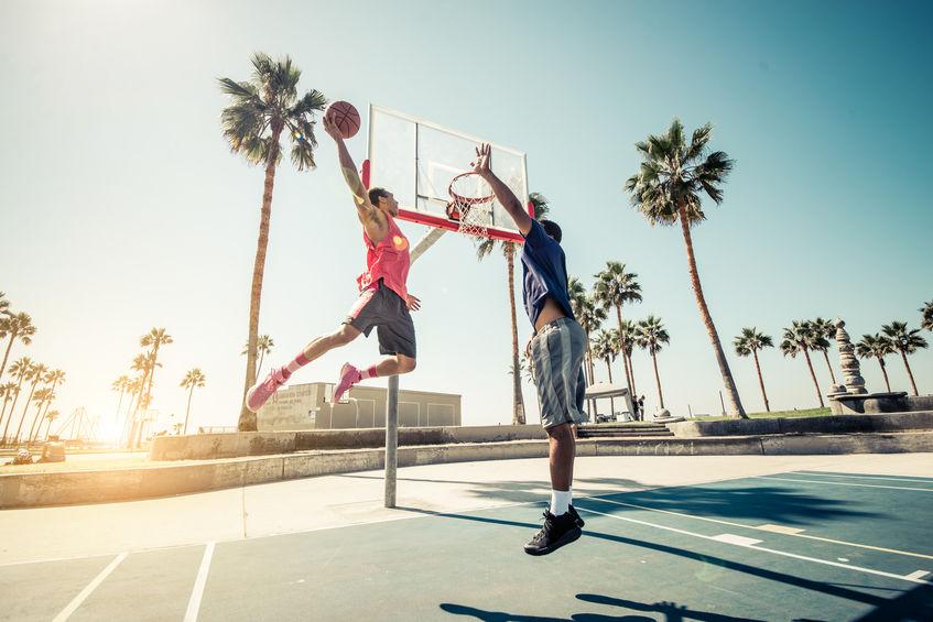 Dois homens jogando basquete em uma quadra de rua