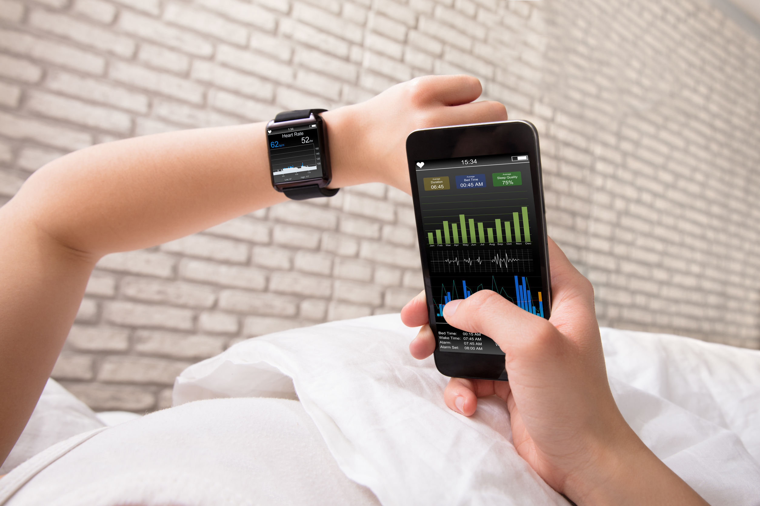 Pessoa deitada conferindo os batimentos cardíacos no relógio e no celular