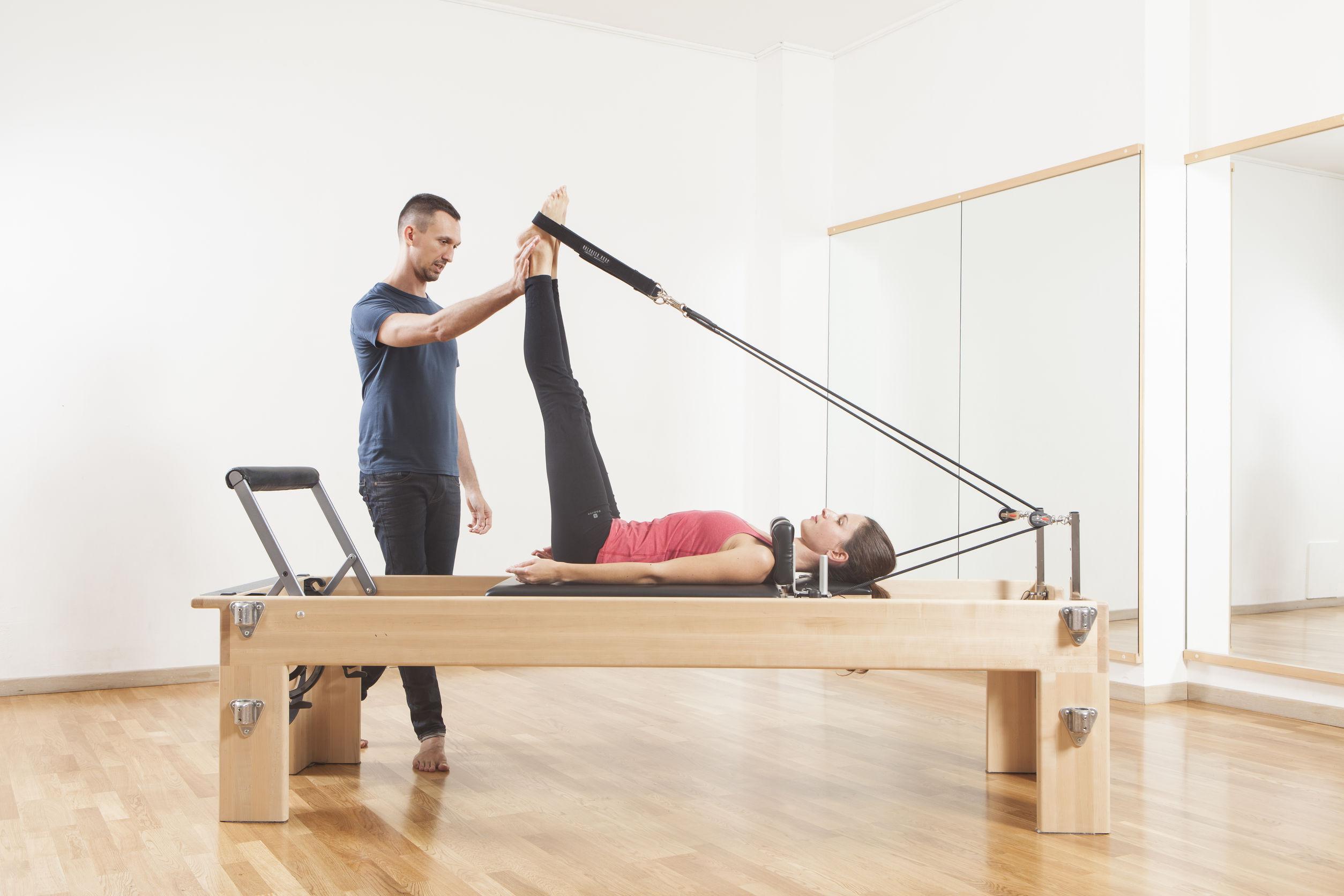 Instrutor ajudando uma aluna a fazer ponte de exercícios físicos.