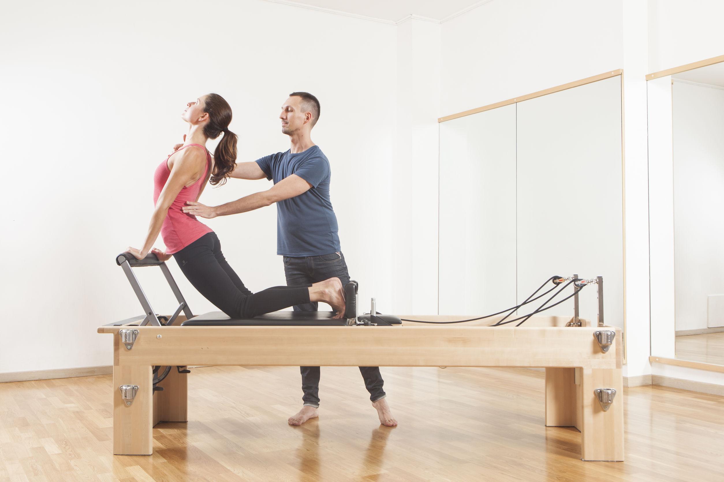 Mulher praticando pilates com ajuda da instrutor.