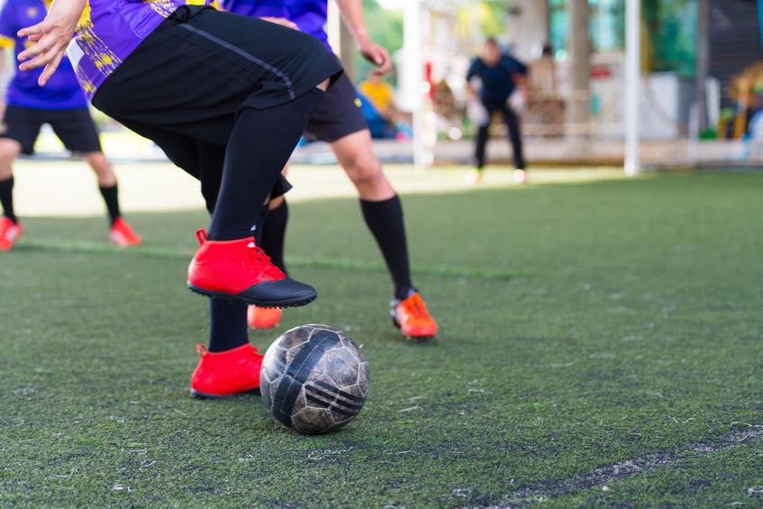 Foto mostra jogadores em um campo de futebol sintético