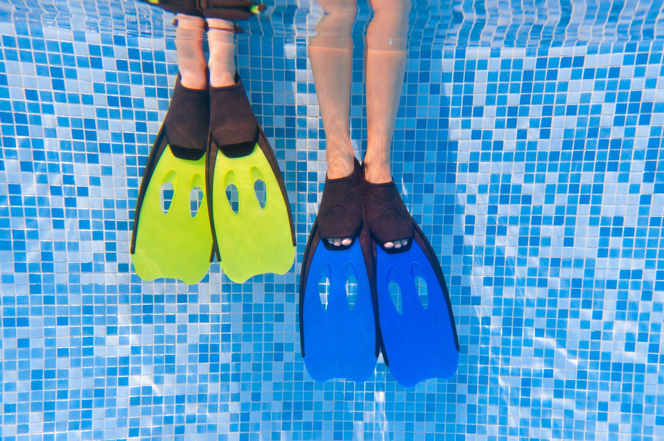 Duas pessoas calçadas com pé de pato na beirada de uma piscina