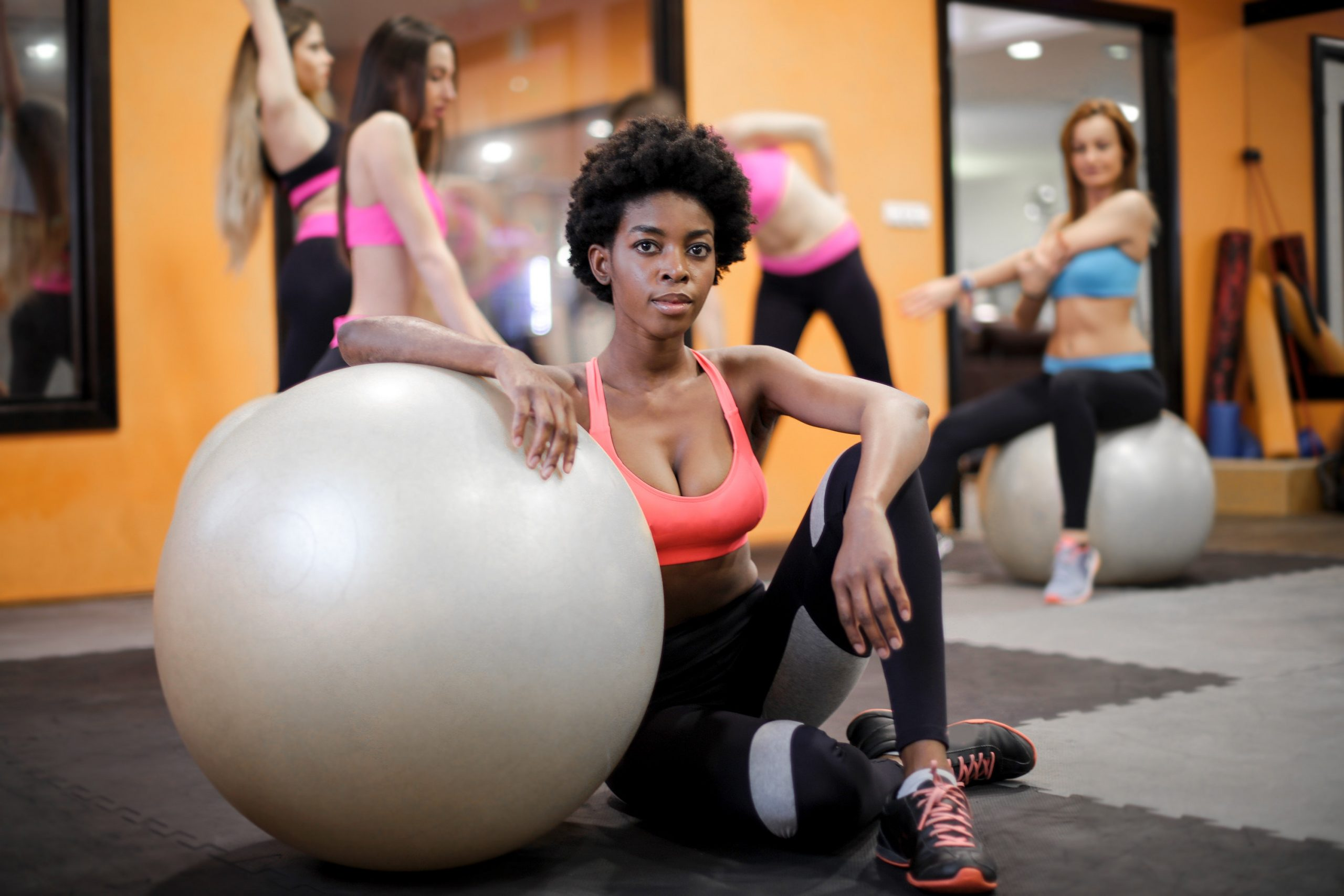 Imagem de uma mulher apoiada em uma bola de pilates.