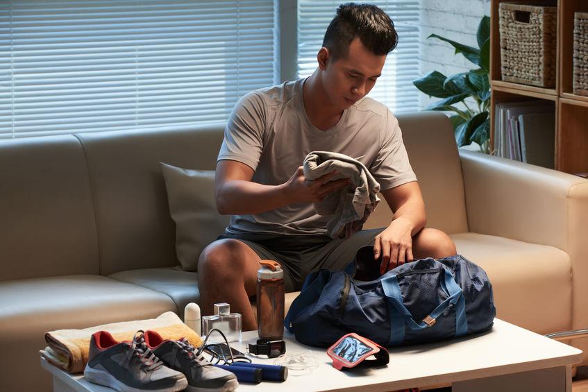 Homem colocando roupas dentro de bolsa esportiva.