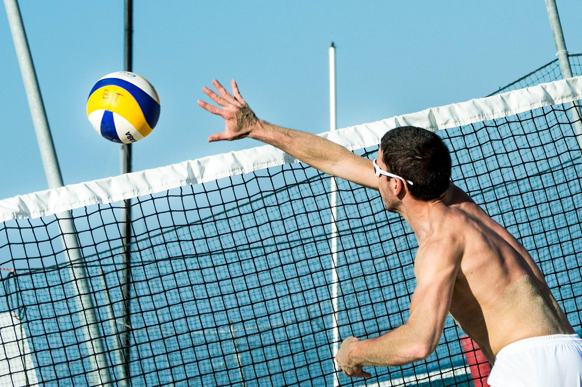 Homem jogando vôlei de praia.
