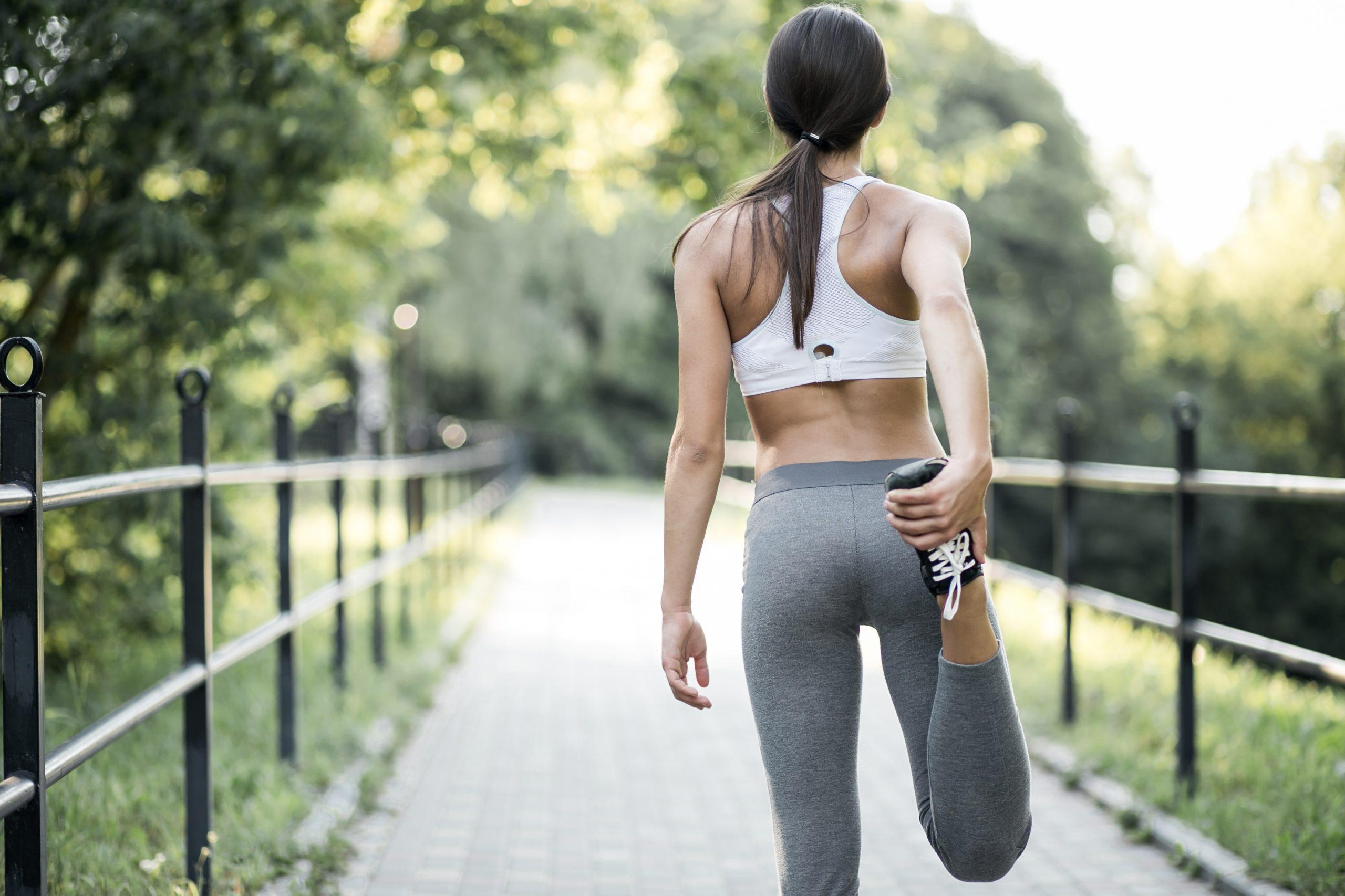 Mulher de costas se aquecendo para correr.