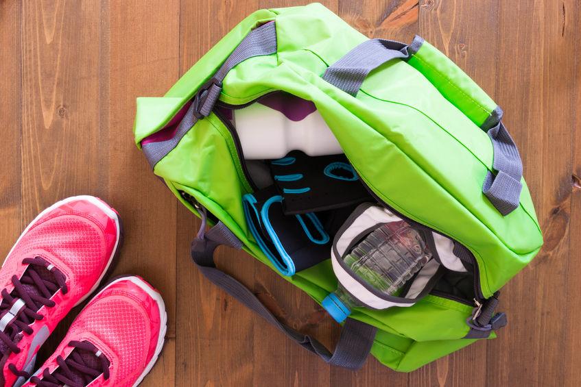 Bolsa esportiva com pertences pessoais e par de tênis.