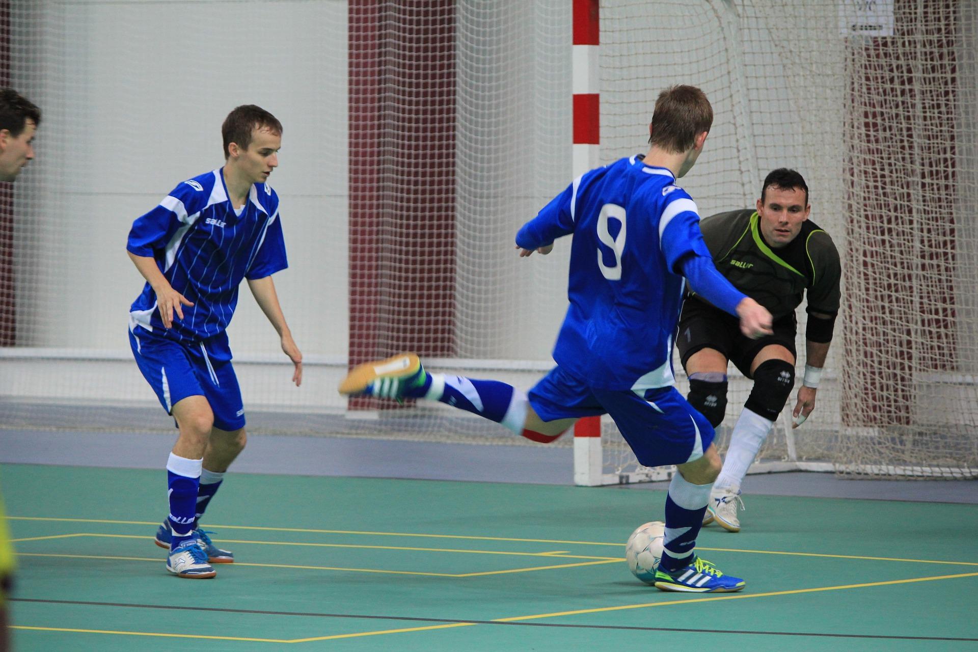 Homens jogando futsal em uma quadra coberta