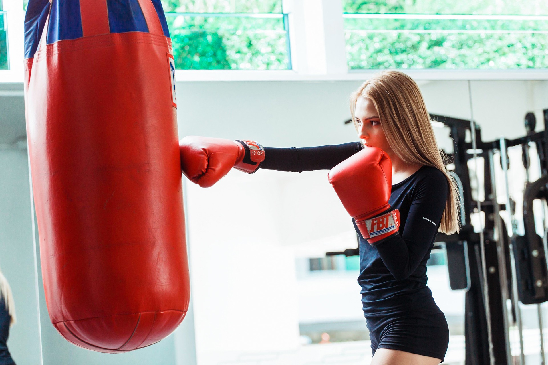 Mulher treinando boxe no saco.