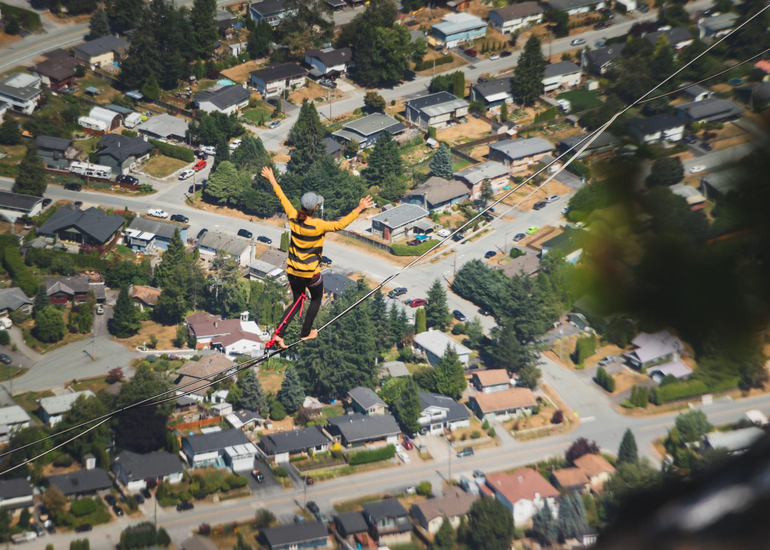 Mulher praticando highline sobre casas.