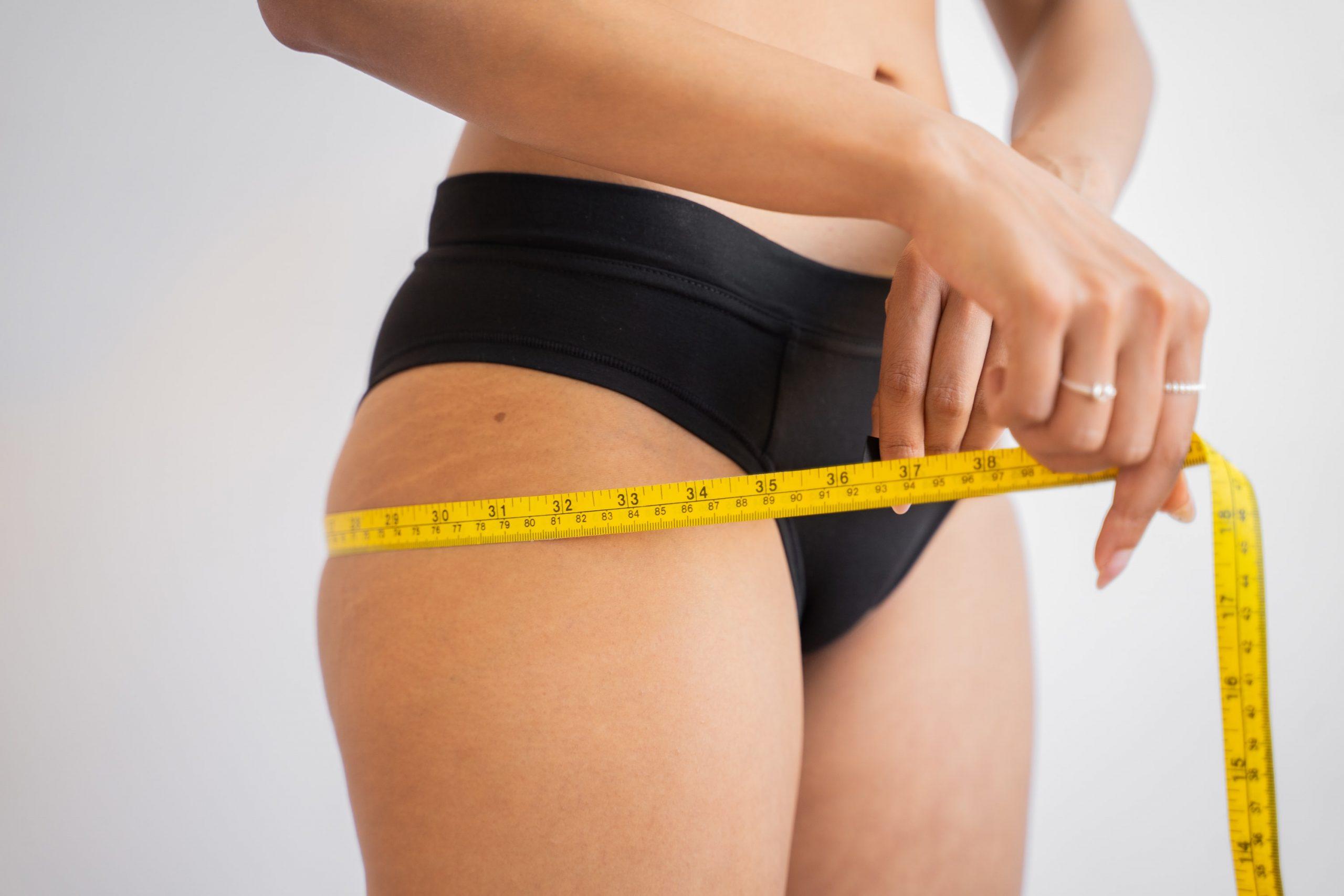 Imagem de uma mulher medindo a circunferência do quadril.