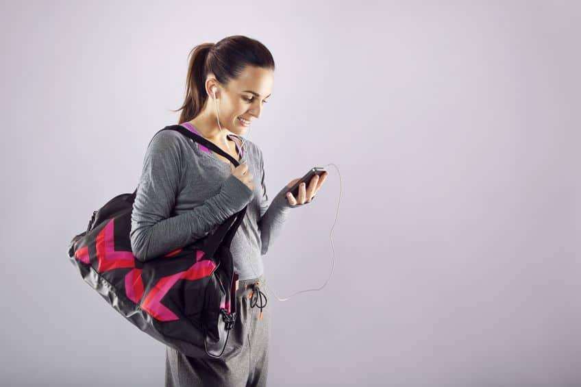 Mulher com bolsa esportiva no ombro, olhando o celular.