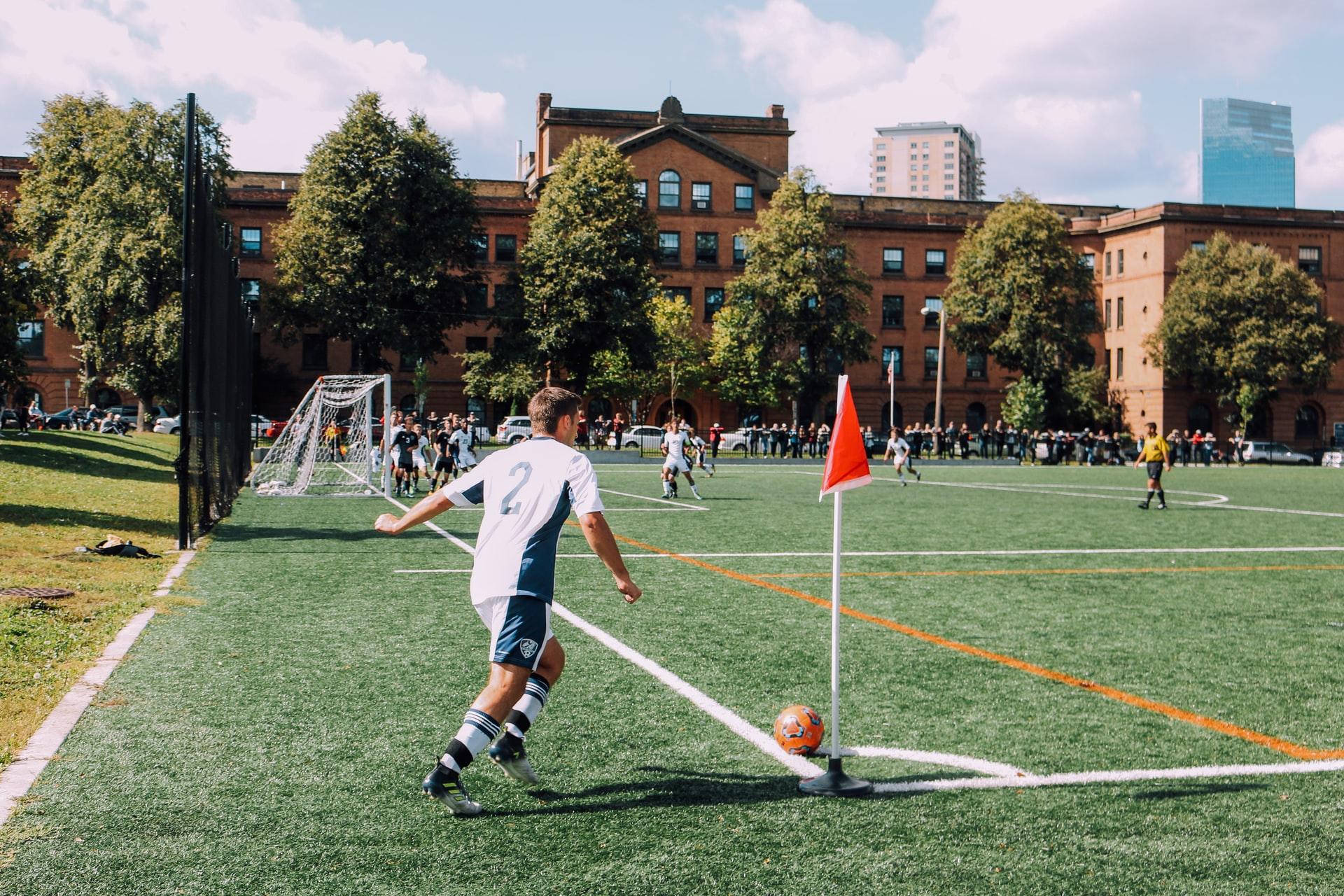 Foto mostra o jogador em direção a bater o escanteio em um campo de grama sintética.